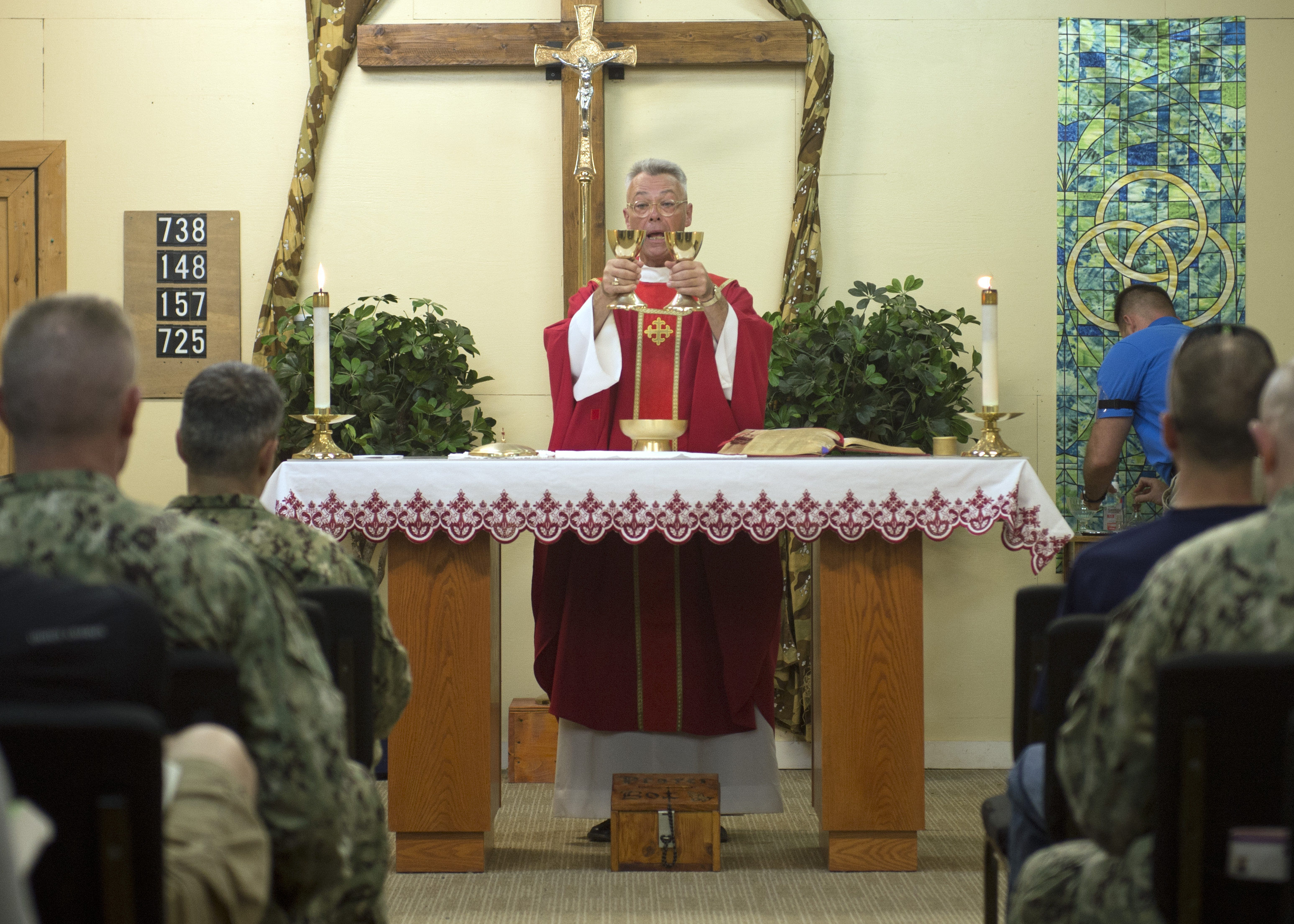 U.S. Navy Chaplain Capt. Sean O'Brien raises chalices as part of a consecration ritual during Catholic mass at Camp Lemonnier, Djibouti, Mar. 28, 2015. The Chaplain's priorities are to enhance Airmen's readiness by preparing them with spiritual resiliency, engaging them through ministry of presence and spiritual care and ensuring worship and religious education opportunities are available to all. (U.S. Air Force photo by Staff Sgt. Kevin Iinuma)