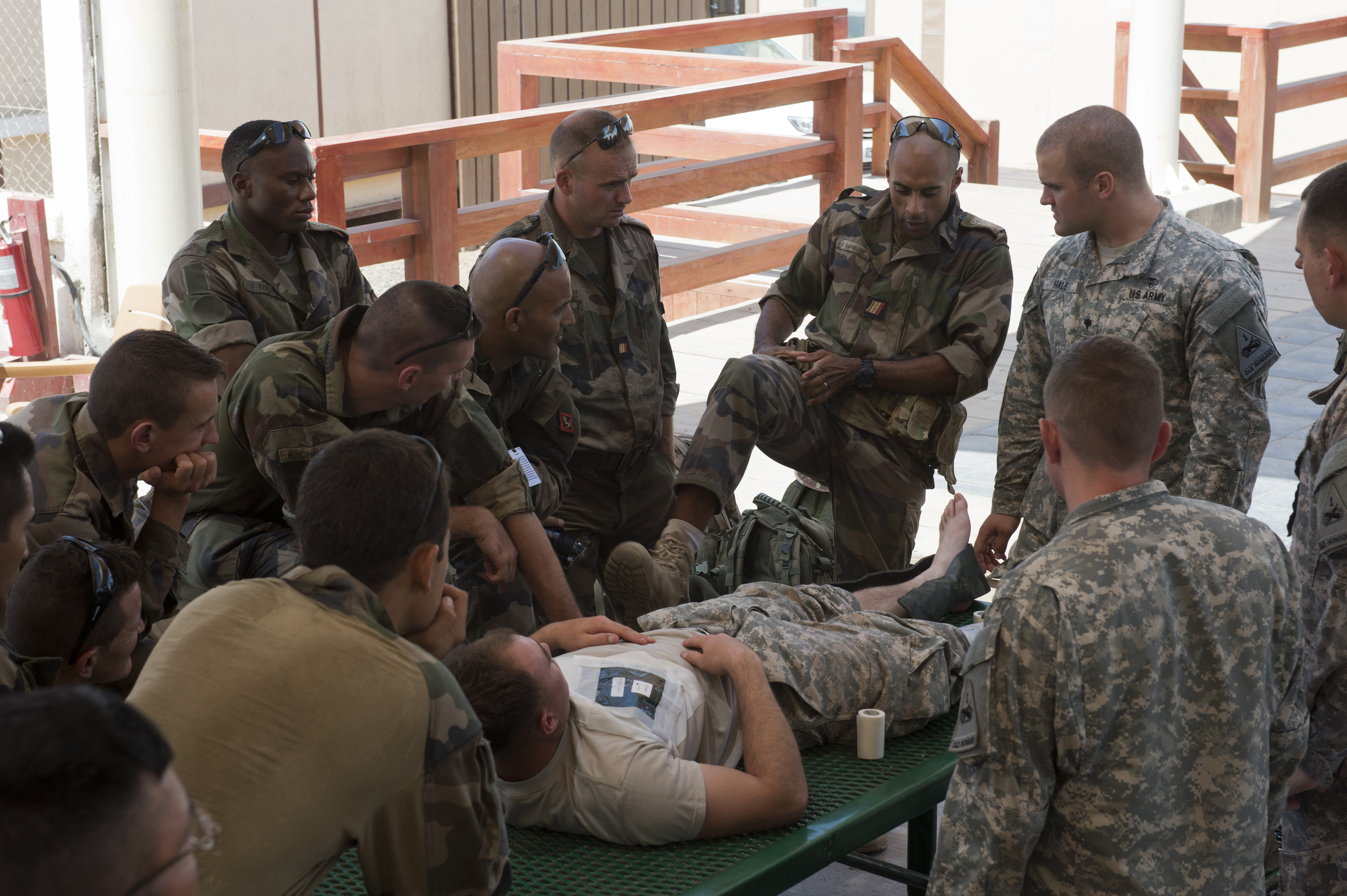 Members of the French 5th Combined Overseas Marines Battalion, compare best practices on splinting a leg under fire in preparation for the Expert Infantry Badge assessment on Camp Lemonnier, Djibouti, April 15, 2015. Tactical Combat Casualty Care is one of many skills soldiers are graded on during the EIB assessment course. (U.S. Air Force photo by Staff Sgt. Nathan Maysonet)