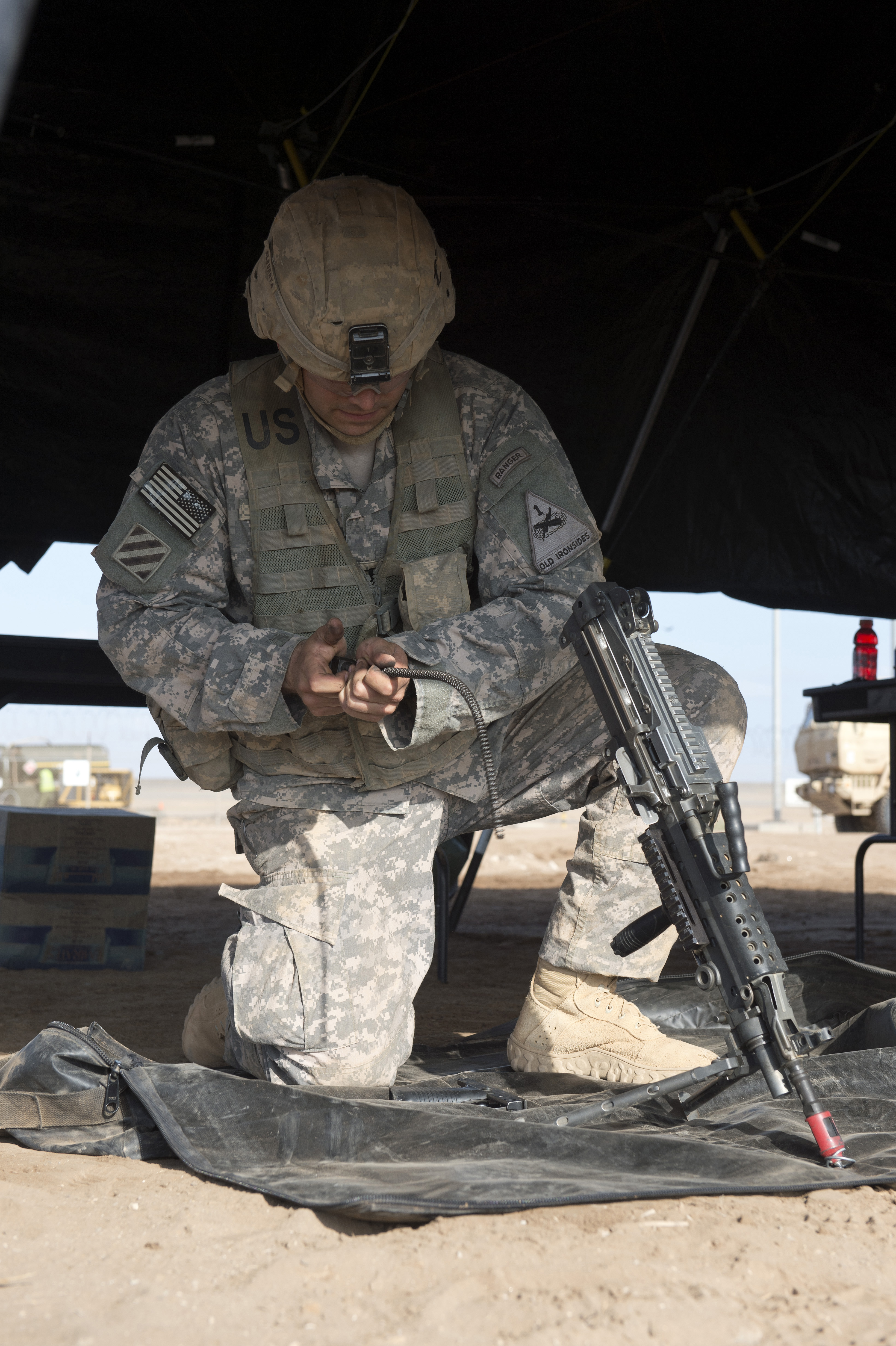 A soldier from the 1st Battalion, 77th Armor Regiment, reassembles a M249 Squad Automatic Weapon during the Expert Infantry Badge assessment course at Camp Lemonnier, Djibouti, April 21, 2015. Candidates' ability to properly maintain and utilize a variety of weapons was graded as part of the EIB assessment. (U.S. Air Force photo by Staff Sgt. Nathan Maysonet)