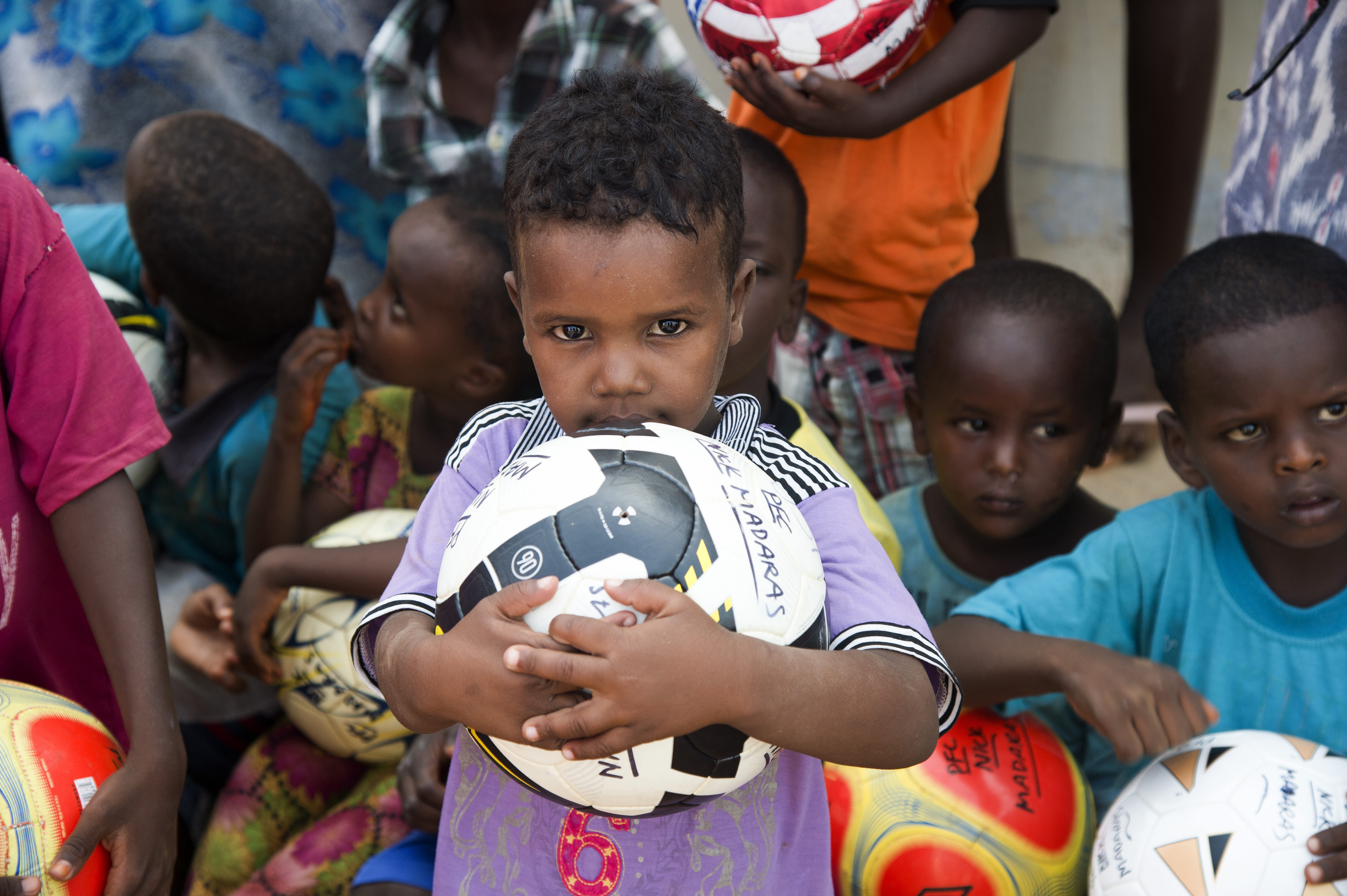 A child holds a soccer ball given to him by volunteers from Combined Joint Task Force-Horn of Africa during a visit by members of the U.S. Army's 404th Civil Affairs Battalion (Airborne), to Chebelley Village, Djibouti, May 21, 2015. Chebelley village is a community near Camp Lemonnier that the 404th CA BN visits monthly for community events and projects. (U.S. Air Force photo by Staff Sgt. Nathan Maysonet)