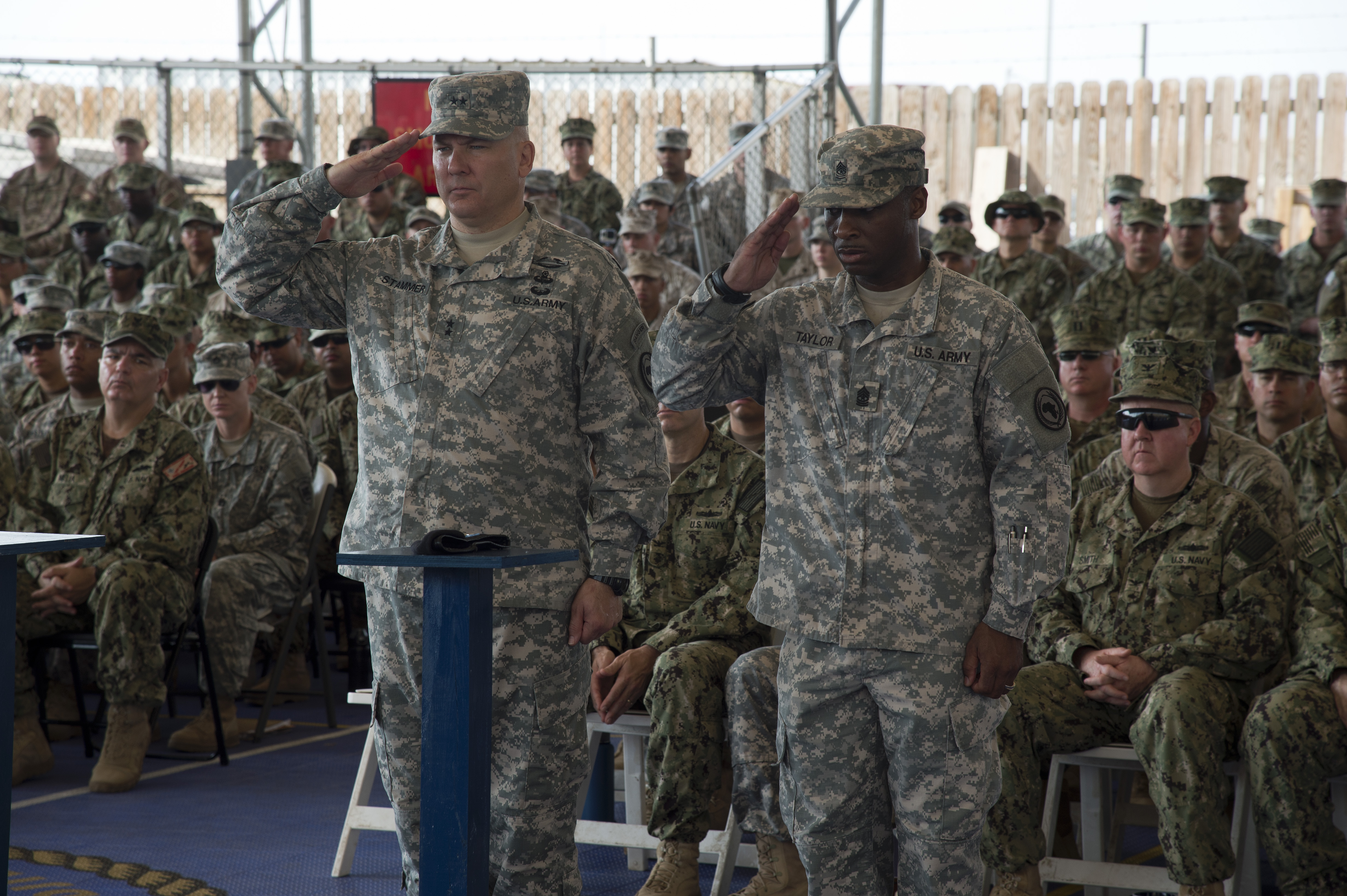 Maj. Gen. Mark Stammer, Combined Joint Task Force-Horn of Africa commander, and Sgt. Maj. Claudell Taylor, CJTF-HOA senior enlisted leader, salute a Memorial Day display at CJTF-HOA, Djibouti, May 25, 2015. The display was in honor of U.S. military personnel who have died in service to their country. (U.S. Air Force photo by Staff Sgt. Nathan Maysonet)