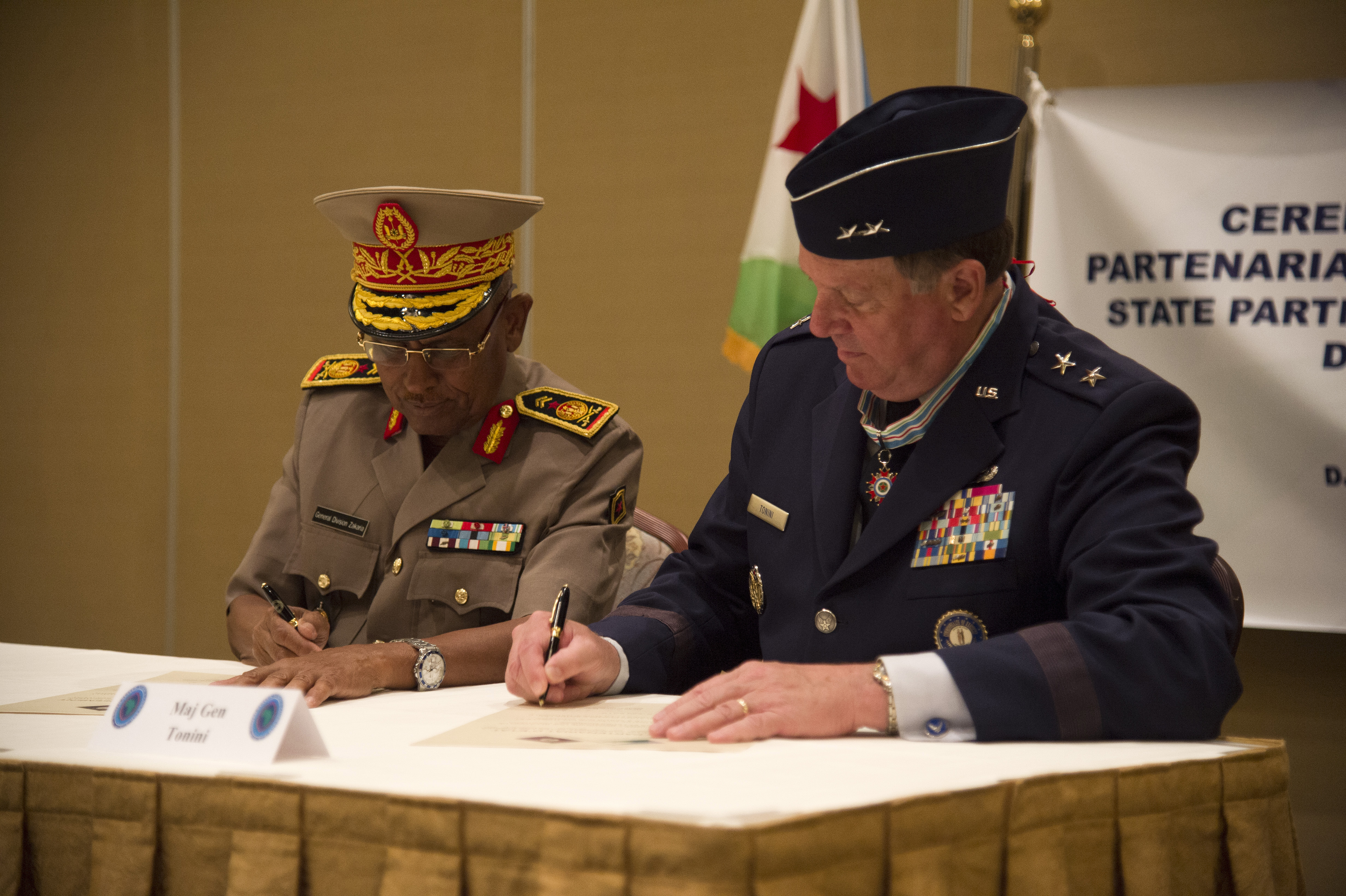 Maj. Gen. Zakaria Cheik Ibrahim, (left), Djiboutian Armed Forces (FAD) chief of defense and Maj. Gen. Edward Tonini, Kentucky National Guard (KNG) adjutant general, sign a State Partnership Program agreement at the Kempinski Hotel, Djibouti, June 2, 2015. The agreement means a long term cooperative agreement between the KNG and FAD that will foster mutually beneficial exchanges between the two at all levels of the military as well as the civilian world. (U.S. Air Force photo by Staff Sgt. Nathan Maysonet)
