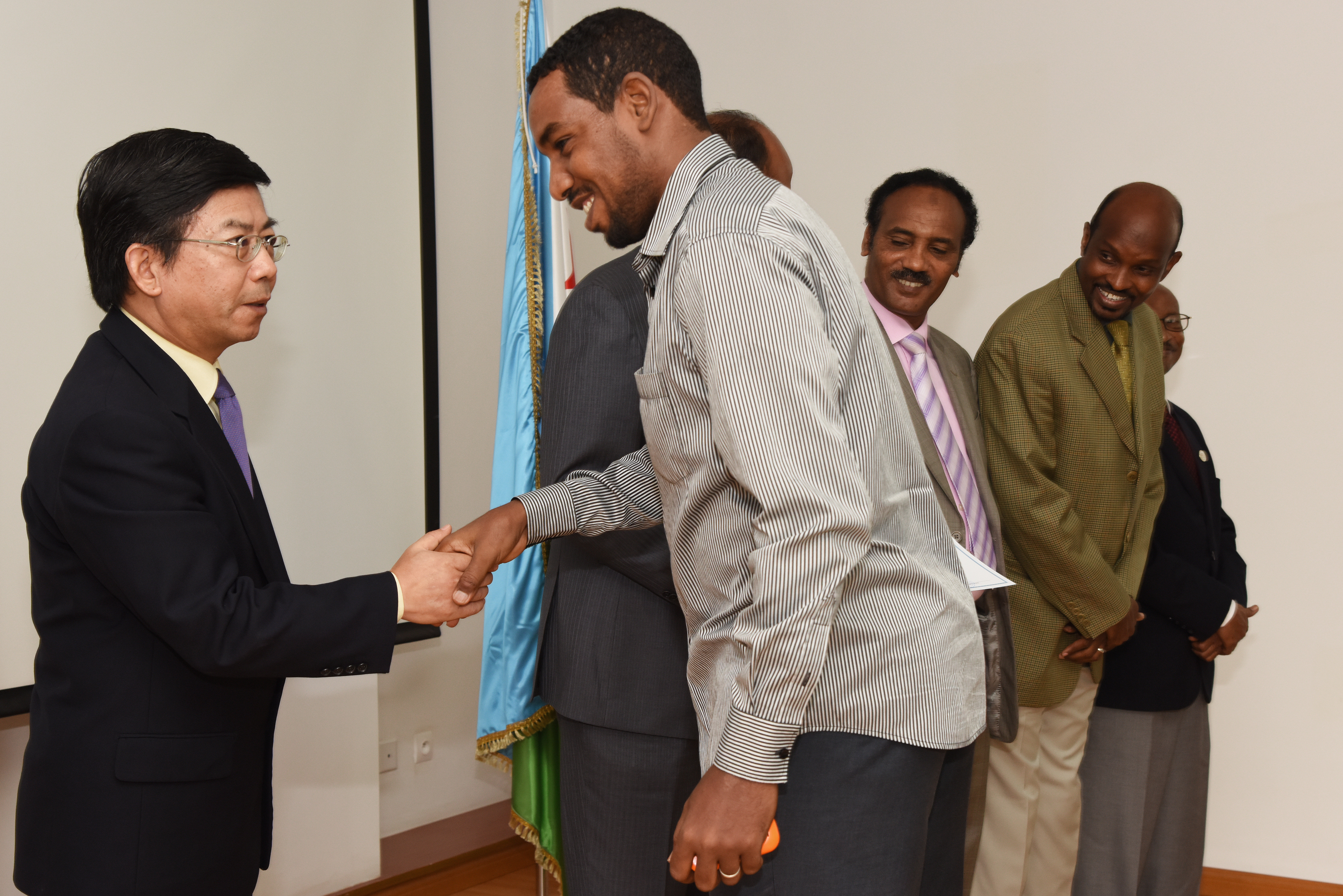 Fu Huaginag, Chinese Ambassador to Djibouti, congratulates a language class student during a graduation ceremony at the Institute of Diplomatic Studies in Djibouti, June 14, 2015.  Some of the graduating students spent the last nine months studying Chinese-Mandarin.  (U.S. Air Force photo by Staff Sgt. Maria Bowman)