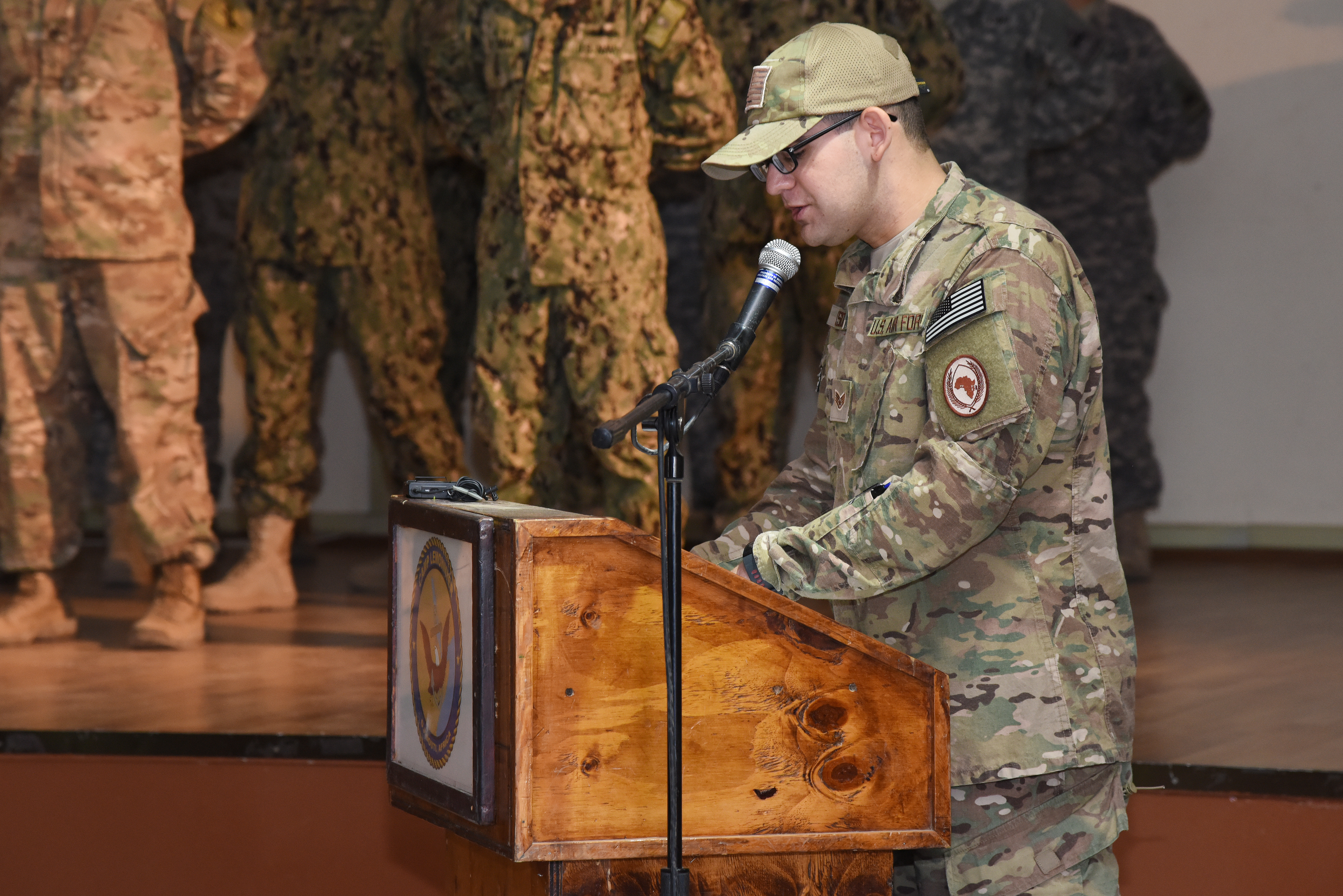 Staff Sgt. Nathan Maysonet, Combined Joint Task Force-Horn of Africa public affairs photojournalist, emcees a relinquishment of authority ceremony at Camp Lemonnier, Djibouti, June 19, 2015.  (U.S. Air Force photo by Staff Sgt. Maria Bowman)
