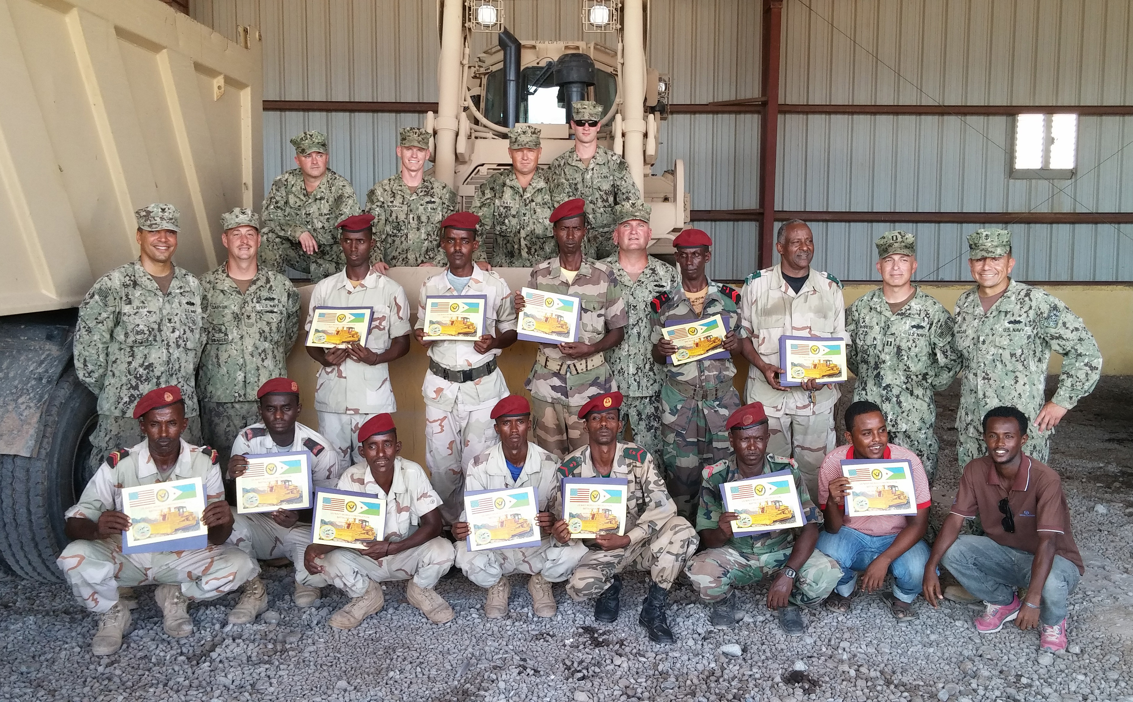 Camp Lemonnier , Djibouti (May 12, 2015) U.S. Navy Seabees of Naval Mobile Construction Battalion (NMCB) 14 pose with members of the Djiboutian Army's Construction Engineers in front of new D7 Dozers after an awards ceremony at the close of a U.S. Army-led training evolution. NMCB-14 Detachment HOA is deployed to Camp Lemonnier in support of Combined Joint Task Force – Horn of Africa. (U.S. Navy photo by Chief Petty Officer Ellery Sayre)