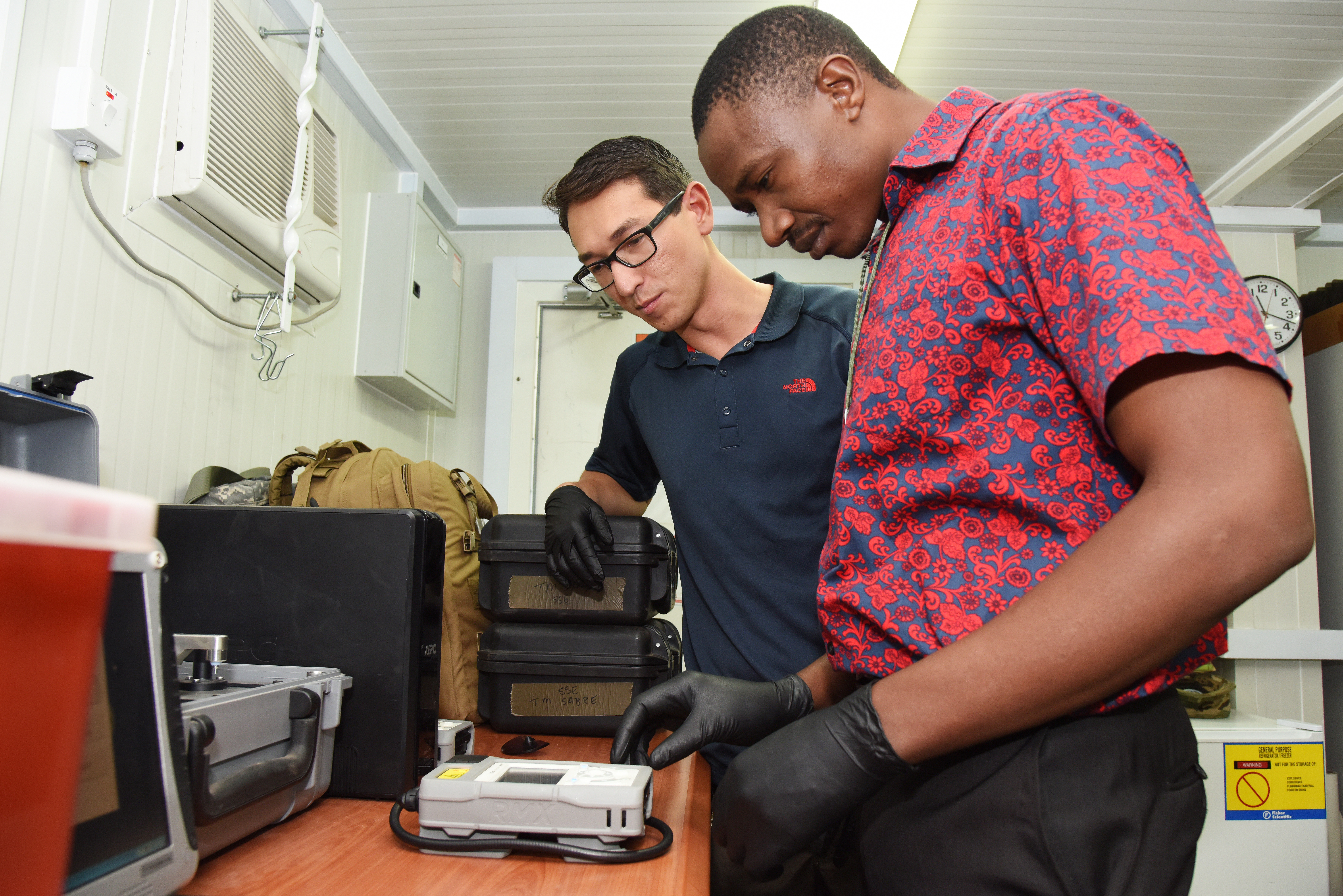 U.S. Army Sgt. Brian Burgess, Joint Theater Forensic Analysis Center case processor, teaches Tanzanian Defense Force Capt. Joram Kinyunyi Chacha how to identify an unknown substance by using a handheld chemical identifier during a class at Camp Lemonnier, Djibouti, June 23, 2015.  Militaries use the machine to quickly identify explosives, industrial chemicals, chemical weapons, narcotics and more.  (U.S. Air Force photo by Staff Sgt. Maria Bowman)