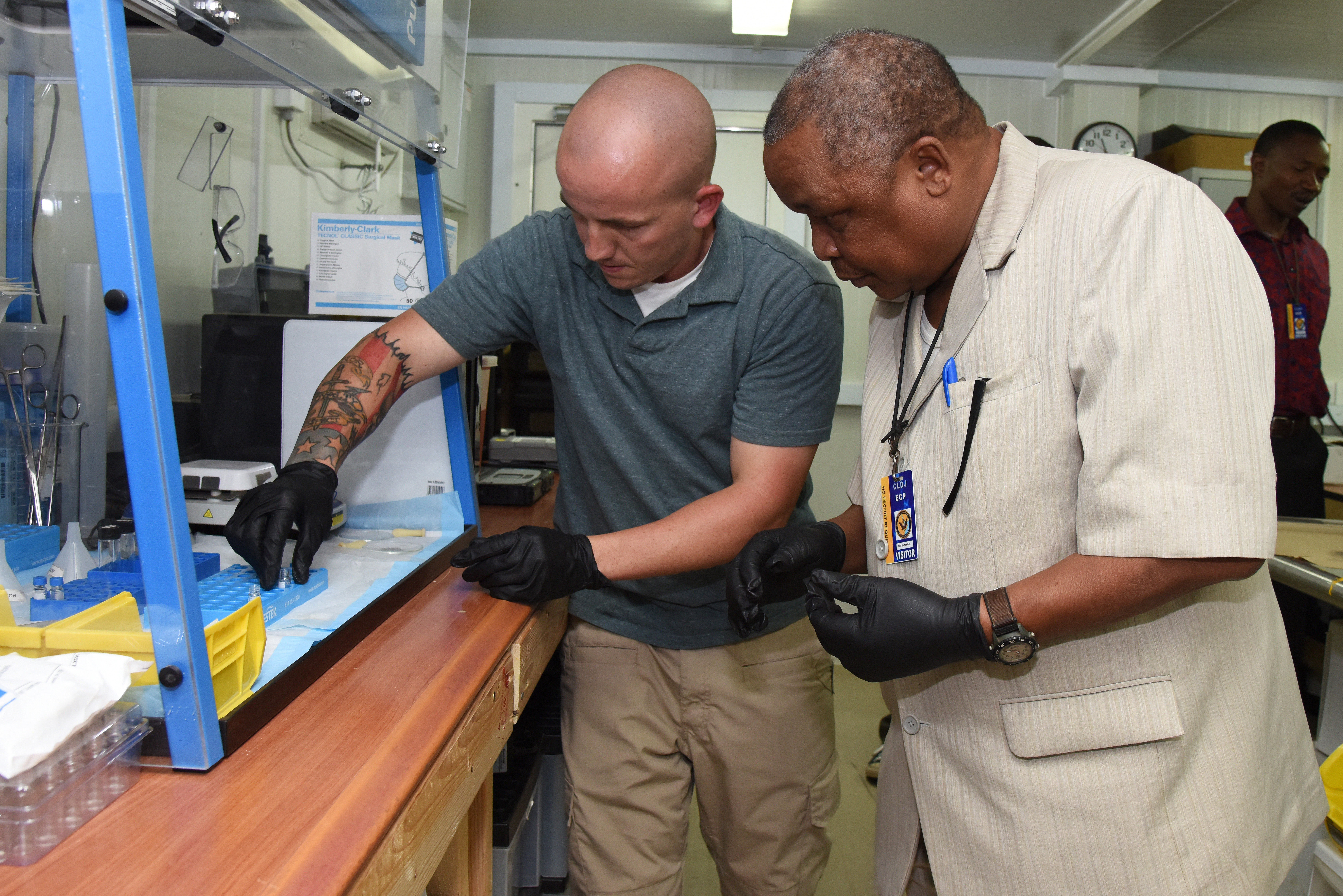 U.S. Army Staff Sgt. Walter Duncan (left), Joint Theater Forensic Analysis Center case manager, demonstrates how to set up samples for the Gas Chromatography Mass Spectrometry to Tanzania Defense Force Col. Abulrasul Ali Fupi, during a forensics briefing at Camp Lemonnier, Djibouti, June 23, 2015.  The JTFAC team uses GC/MS to identify different substances within a test sample. It can be used to aid with drug detection, fire investigation, explosives investigation, and identification of unknown samples.  (U.S. Air Force photo by Staff Sgt. Maria Bowman)