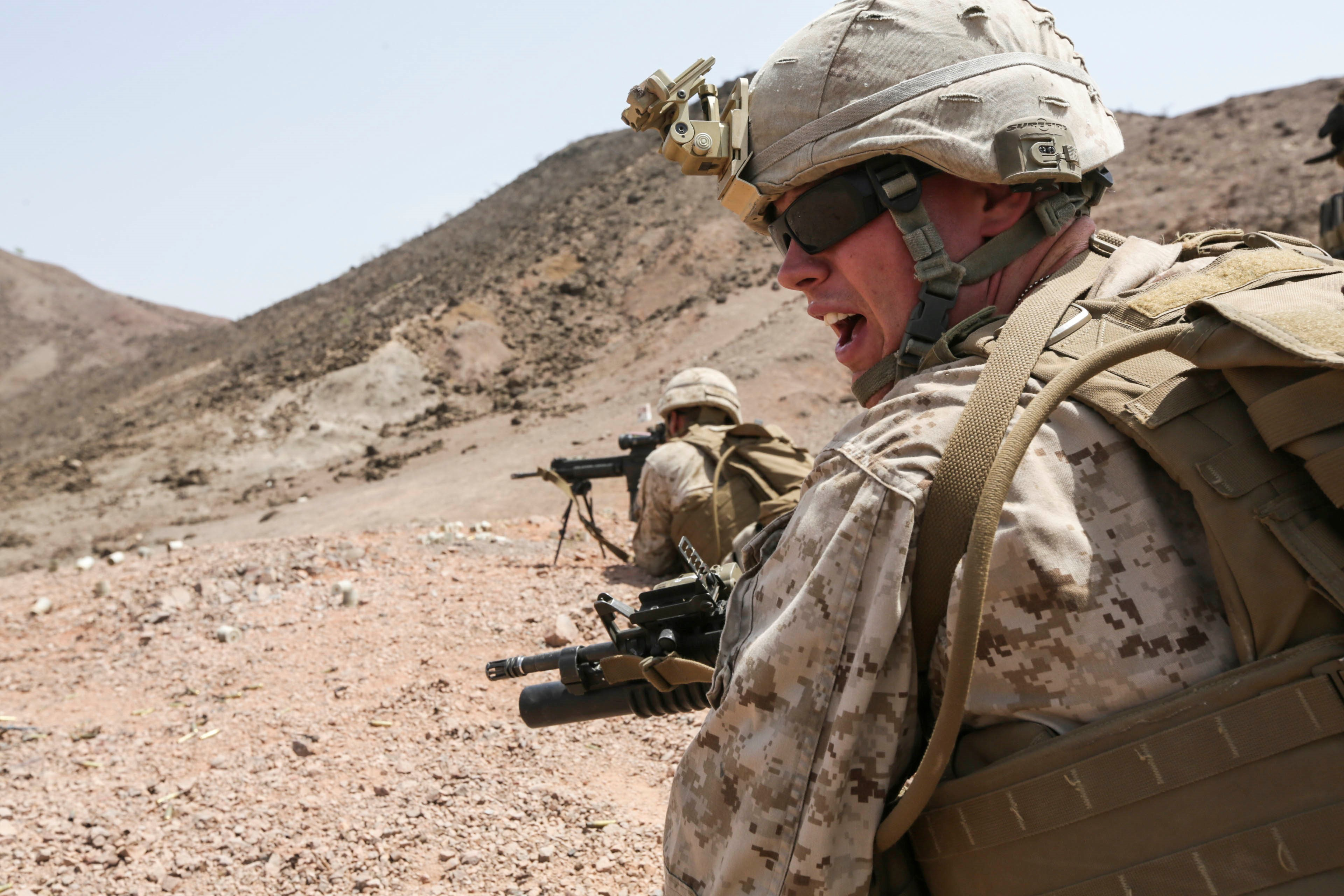 ARTA BEACH, Djibouti (July 22, 2015) A U.S. Marine team leader with Battalion Landing Team 3rd Battalion, 1st Marine Regiment, 15th Marine Expeditionary Unit, yells commands to his squad during a squad-attack exercise.  The Marines of BLT 3/1 executed a series of attack and maneuver drills consisting of, machine gun, squad and night attacks.  Elements of the 15th Marine Expeditionary Unit are ashore in Djibouti for sustainment training to maintain and enhance the skills they developed during their pre-deployment training period.  The 15th MEU is currently deployed in support of maritime security operations and theater security cooperation efforts in the U.S. 5th and 6th Fleet areas of operation. (U.S. Marine Corps photo by Sgt. Jamean Berry/Released)