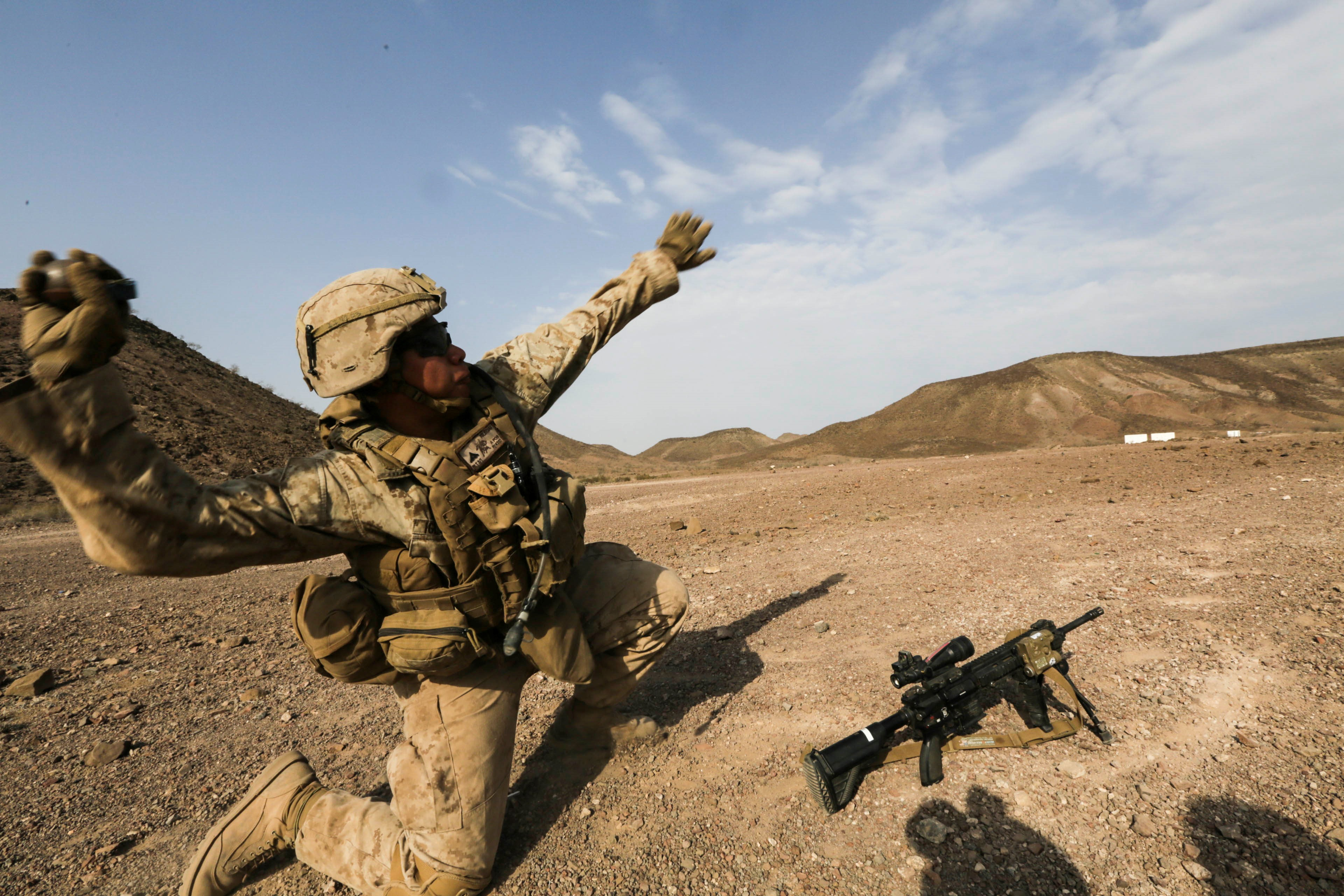 ARTA BEACH, Djibouti (July 22, 2015) A U.S. Marine with Battalion Landing Team 3rd Battalion, 1st Marine Regiment, 15th Marine Expeditionary Unit throws a practice grenade during a grenade accuracy exercise.  Elements of the 15th Marine Expeditionary Unit are ashore in Djibouti for sustainment training to maintain and enhance the skills they developed during their pre-deployment training period.  The 15th MEU is currently deployed in support of maritime security operations and theater security cooperation efforts in the U.S. 5th and 6th Fleet areas of operation. (U.S. Marine Corps photo by Sgt. Jamean Berry/Released)