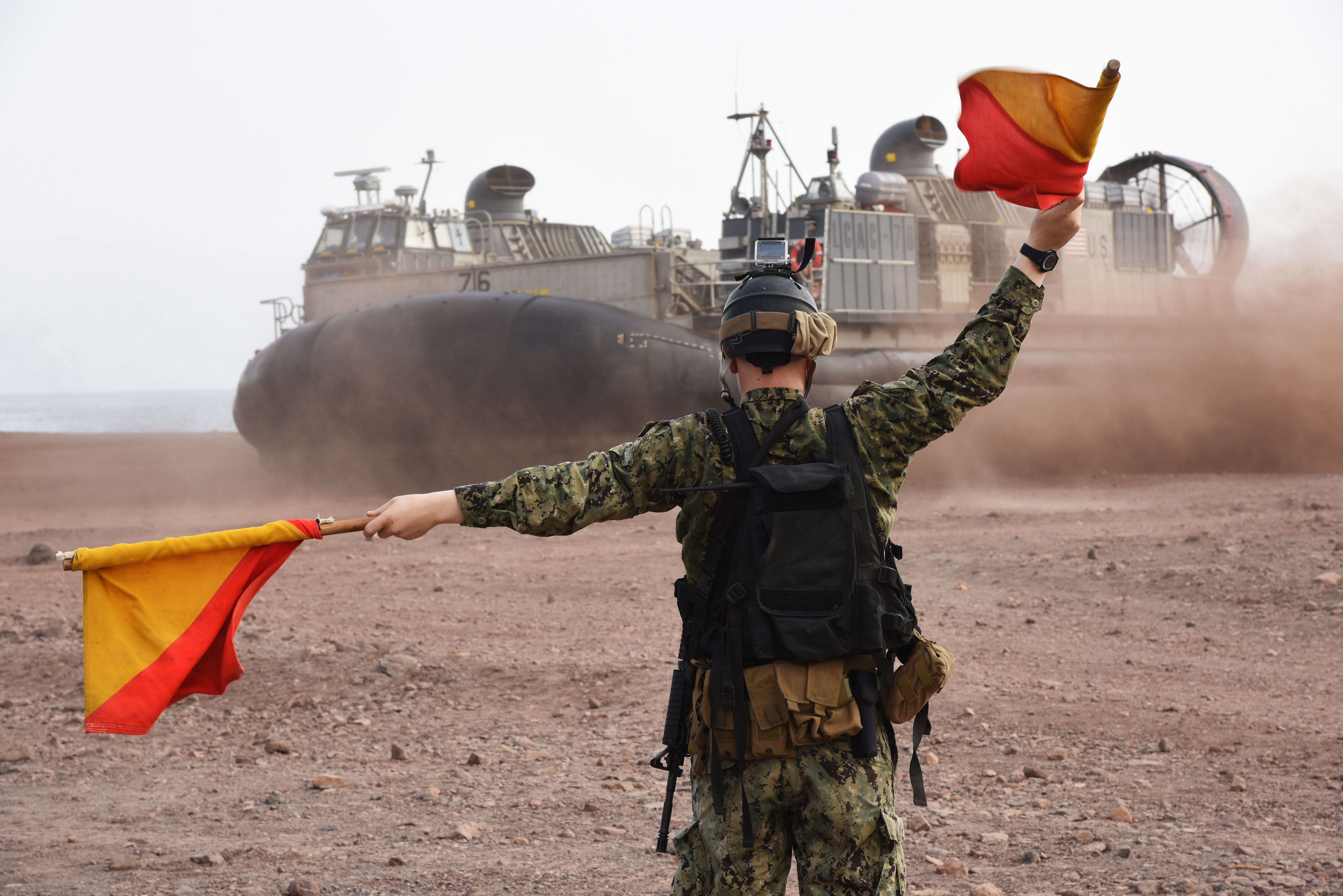 A U.S. Navy Maritime Expeditionary Security Force member signals that it is safe for a U.S. Navy Landing Craft Air Cushion (LCAC) to leave the beach and travel back to the San Antonio-class amphibious transport dock ship USS Anchorage (LPD-23) in Arta, Djibouti, July 20, 2015. LCACs for this military ship delivered U.S. Marines and equipment from the 15th Marine Expeditionary Unit for sustainment training. (U.S. Air Force photo by Staff Sgt. Maria Bowman)