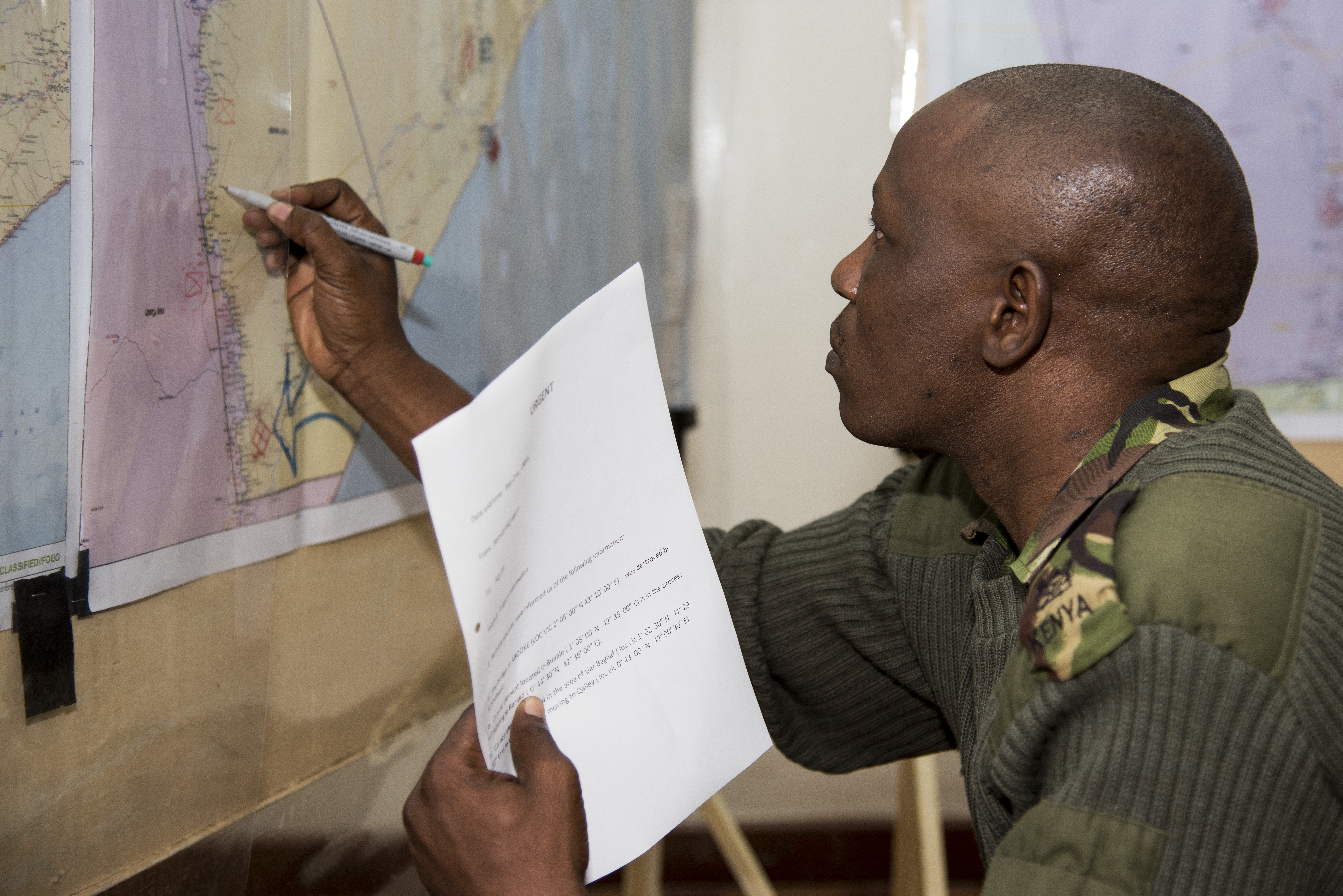 Kenyan Defense Force Maj. Balata Kotea, Africa Contingency Operations Training & Assistance (ACOTA) African Union Mission in Somalia (AMISOM) Force Headquarters training course attendee, updates a map of Somalia with the latest AMISOM and Al-Shabaab troop movements at the International Peace Support Training Center in Nairobi, Kenya, Aug. 25, 2015. Kenya is one of the AU countries contributing to the forces in Somalia battling Al-Shabaab and the ACOTA course helps familiarize the attending officers with the military decision making process, so they can better advise and prepare solutions to the problems they might face in the field. (U.S. Air Force photo by Staff Sgt. Nathan Maysonet/released)