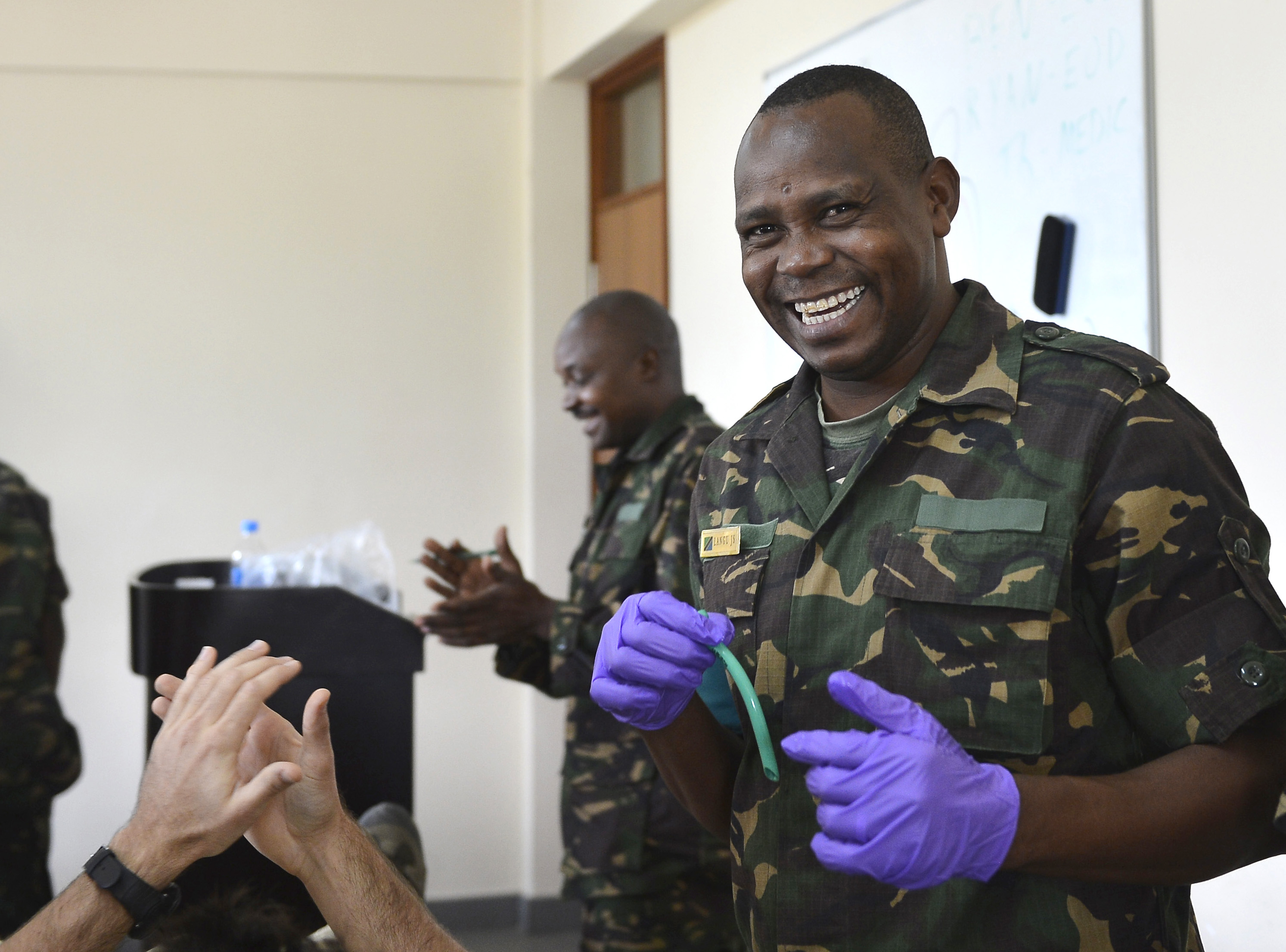Cpl. Joseph S. Langu, Tanzania People's Defense Force ammunition technician, holds a nasopharyngeal airway during a tactical combat casualty  care first aid course at the Peace Keeping Training Center in Dar es Salaam, Tanzania Aug. 23, 2015. TPDF hosted a Humanitarian Action Course where U.S. Navy Explosive Ordnance Disposal technicians, assigned to Combined Joint Task Force-Horn of Africa, shared best practices on medical procedures, ordnance safety and identification.