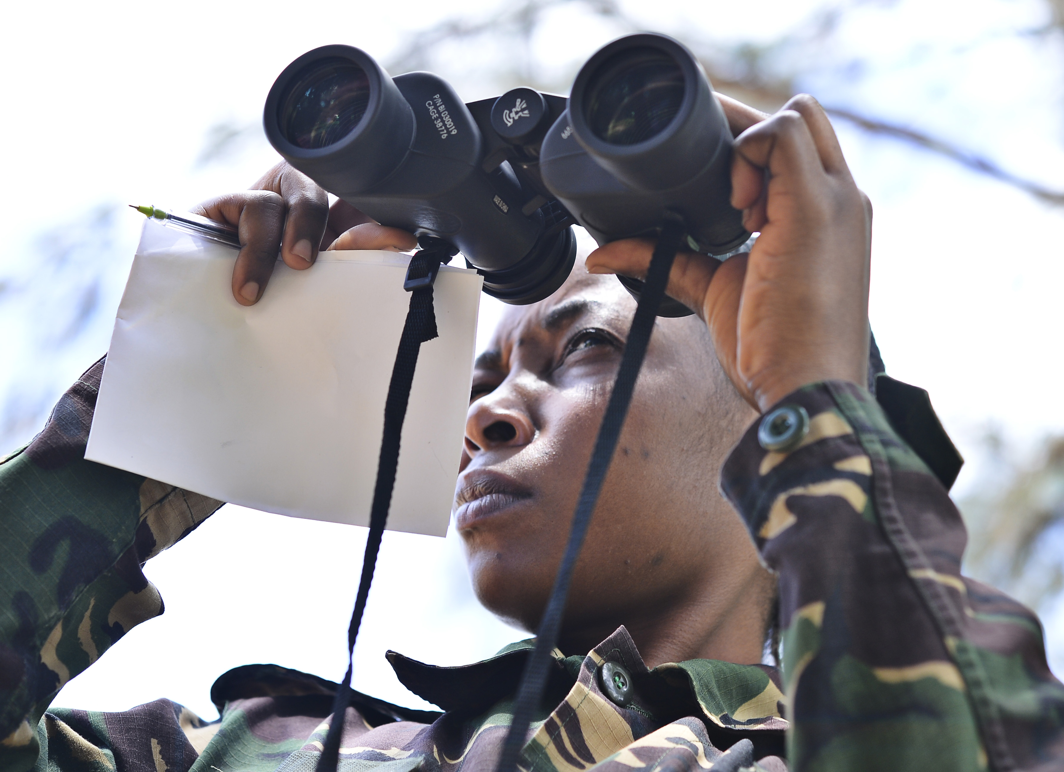 Pvt. Flora Flowin Mkinga, Tanzania People's Defense Force ammunition technician, looks through binoculars during a reconnaissance practical at the Peace Keeping Training Center in Dar es Salaam, Tanzania Aug. 23, 2015. U.S. Navy Explosive Ordnance Disposal technicians, assigned to Combined to Joint Task Force-Horn of Africa, instructed Humanitarian Mine Action course students on ordnance safety and identification and tactical combat casualty care procedures.(U.S. Air Force photo by Senior Airman Nesha Humes)