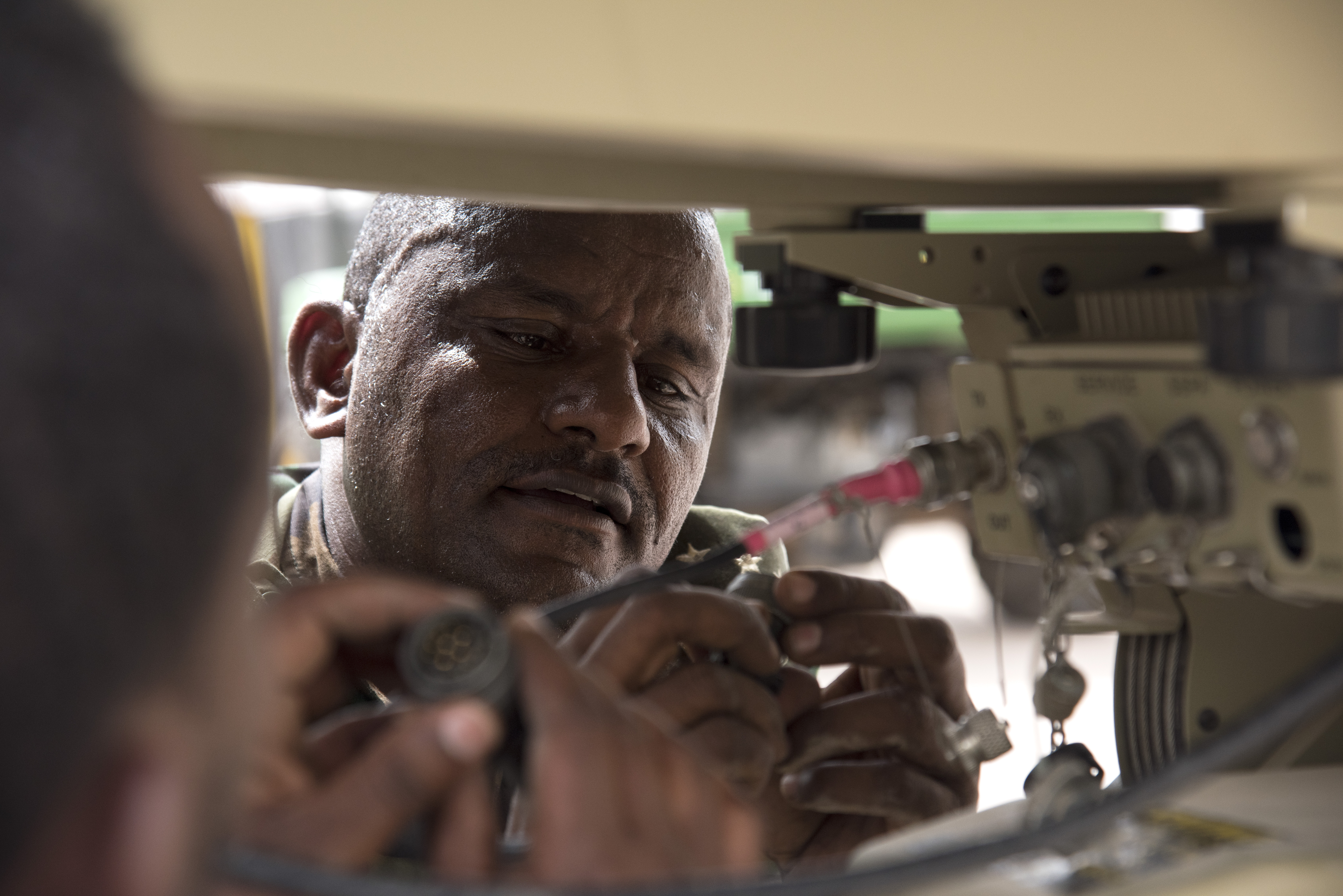 A member of the Ethiopian National Defense Force (ENDF) checks a cable connector during the setup of a U.S. Africa Command Data Sharing Network (ADSN) terminal at Camp Lemonnier, Djibouti, Aug. 18, 2015. ENDF personnel were tested on how quickly they could setup and tear down the field communication system as part of a multi-week ADSN course, which was hosted by Combined Joint Task Force-Horn of Africa communications and intelligence personnel, and was designed to broaden communication interoperability between host nation security forces. (U.S. Air Force photo by Staff Sgt. Nathan Maysonet/released)