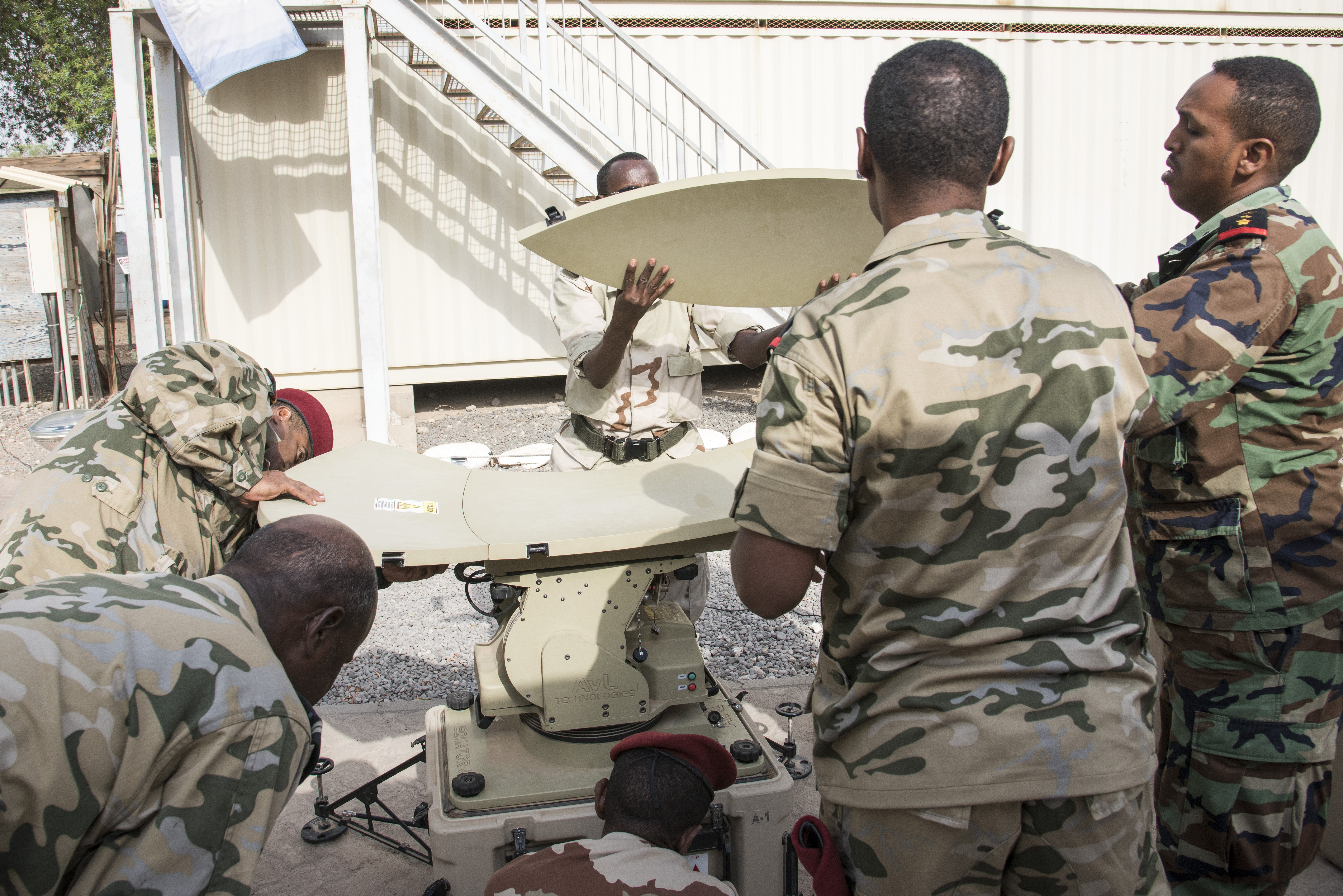 Members of the Djibouti Armed Forces (FAD) assemble the dish of a U.S. Africa Command Data Sharing Network (ADSN) terminal at Camp Lemonnier, Djibouti, Aug 31, 2015.  The ADSN terminal is an enclosed network, meaning it never connects to the internet, and is used by African Mission in Somali forces for field communications. Its setup and use was part of a multi-week ADSN course designed to broaden communication interoperability between host nation security forces, and was hosted by communications and intelligence personnel assigned to Combined Joint Task Force-Horn of Africa. (U.S. Air Force photo by Staff Sgt. Nathan Maysonet/released)