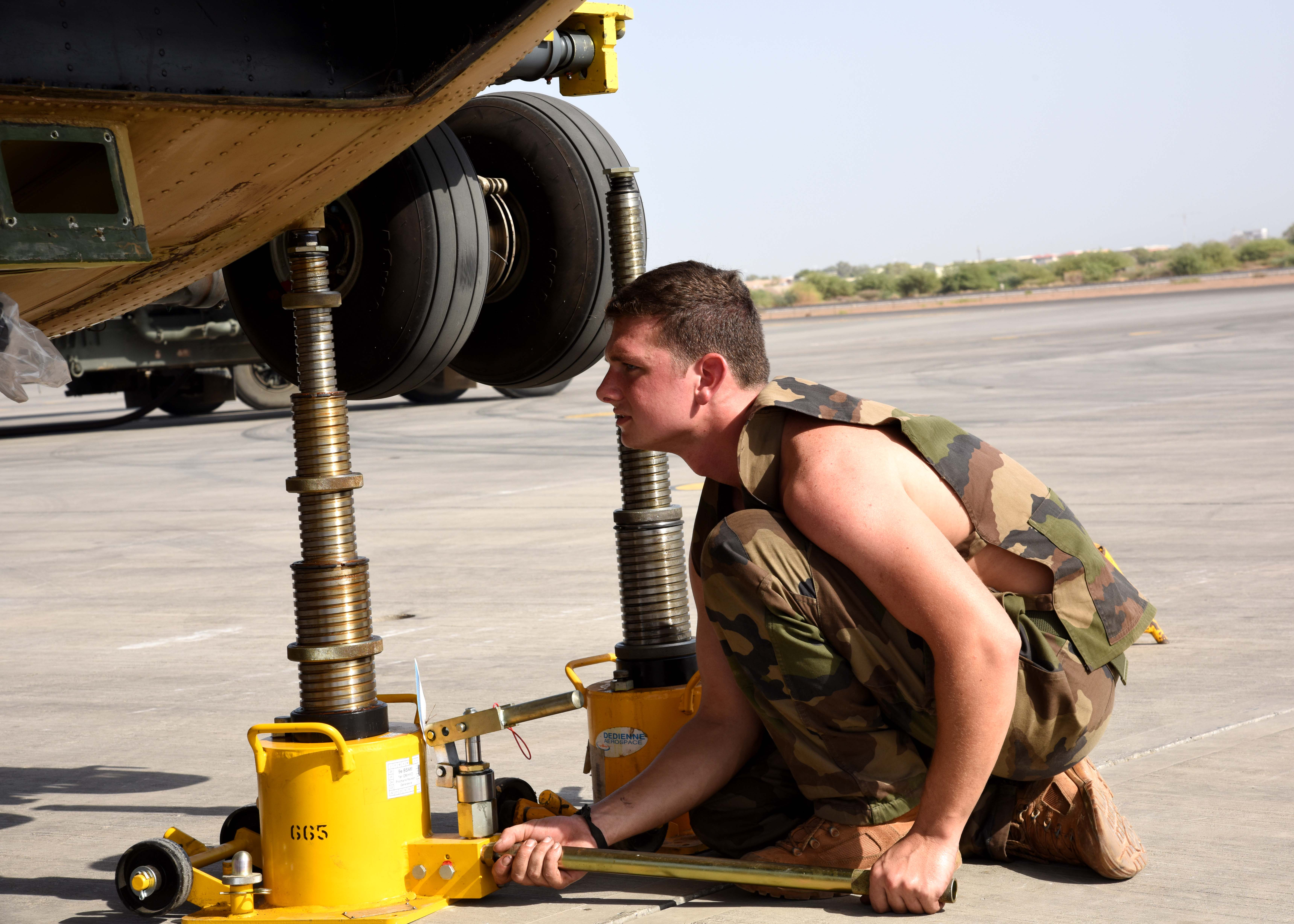 150823-N-DJ346-008 CAMP LEMONNIER, Djibouti (August 23, 2015) French Army crew member  makes wheel adjustments. French and U.S. service members prepare to transport two French Puma Helicopters and associated Passengers & Cargo to N'Djamena aboard a U.S. Air Force C-17 Globemaster. The helicopters support French operations at the intersecting borders of Libya, Chad and Niger deterring weapons and drug smuggling, and jihadist regularly crossing between nations. This is the first time France has received support from U.S. Forces in Djibouti for any mission outside of East Africa. (U.S. Navy photo by Chief Mass Communication Specialist Donald W. Randall/Released)
