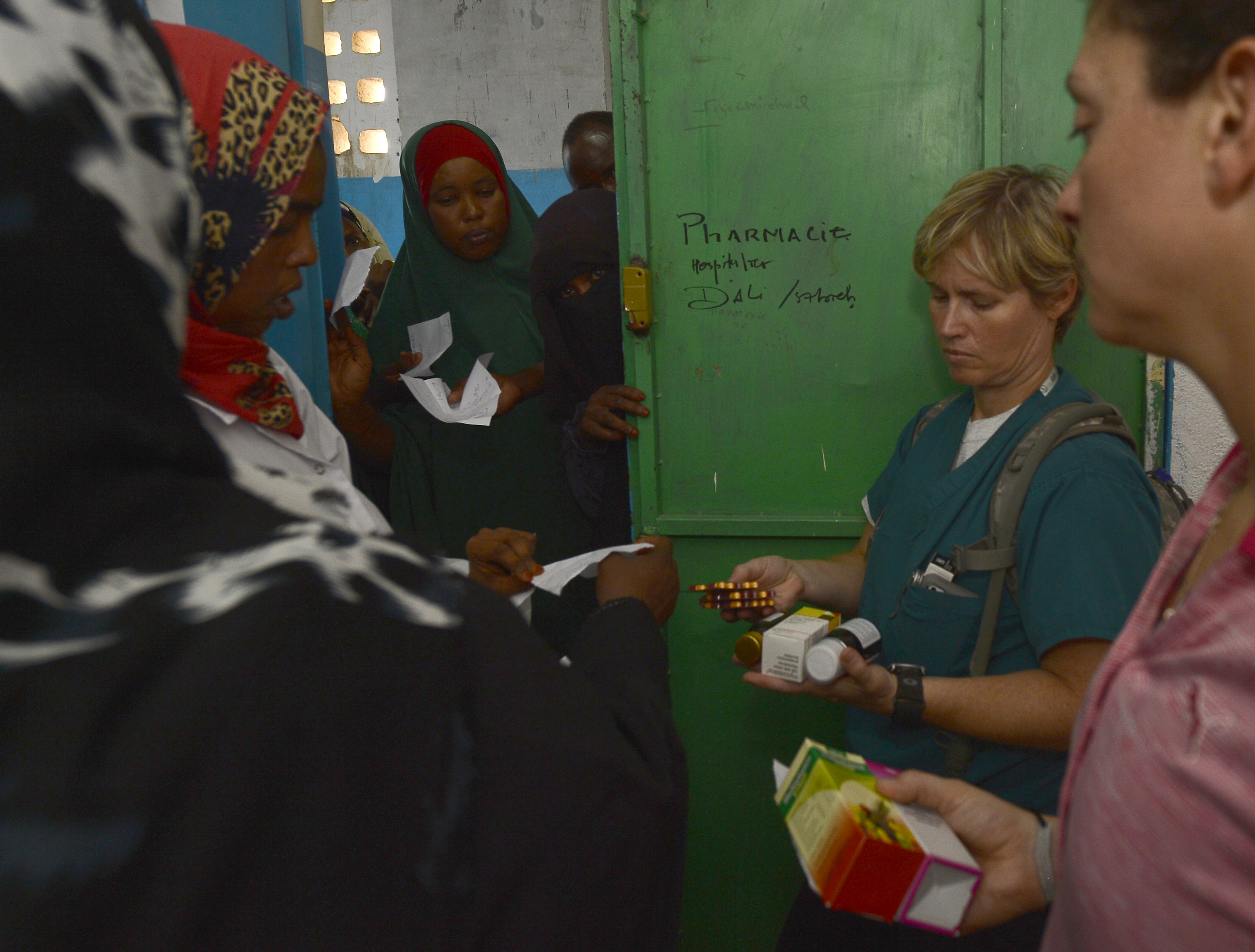 U.S. Army Lt. Col. Patricia Rasmussen, 404th Civil Affairs Battalion veterinarian, center, helps to distribute pharmaceutical medicine during a Medical Civic Action Program at Ali Sabieh Medical Clinic in Djibouti, Africa, Sept. 12, 2015. The 404th CA BN team, assigned to Combined Joint Task Force-Horn of Africa, partnered with Djibouti's Ministry of Health to provide specialty medical care to more than 400 Djiboutians. (U.S. Air Force photo by Senior Airman Nesha Humes)