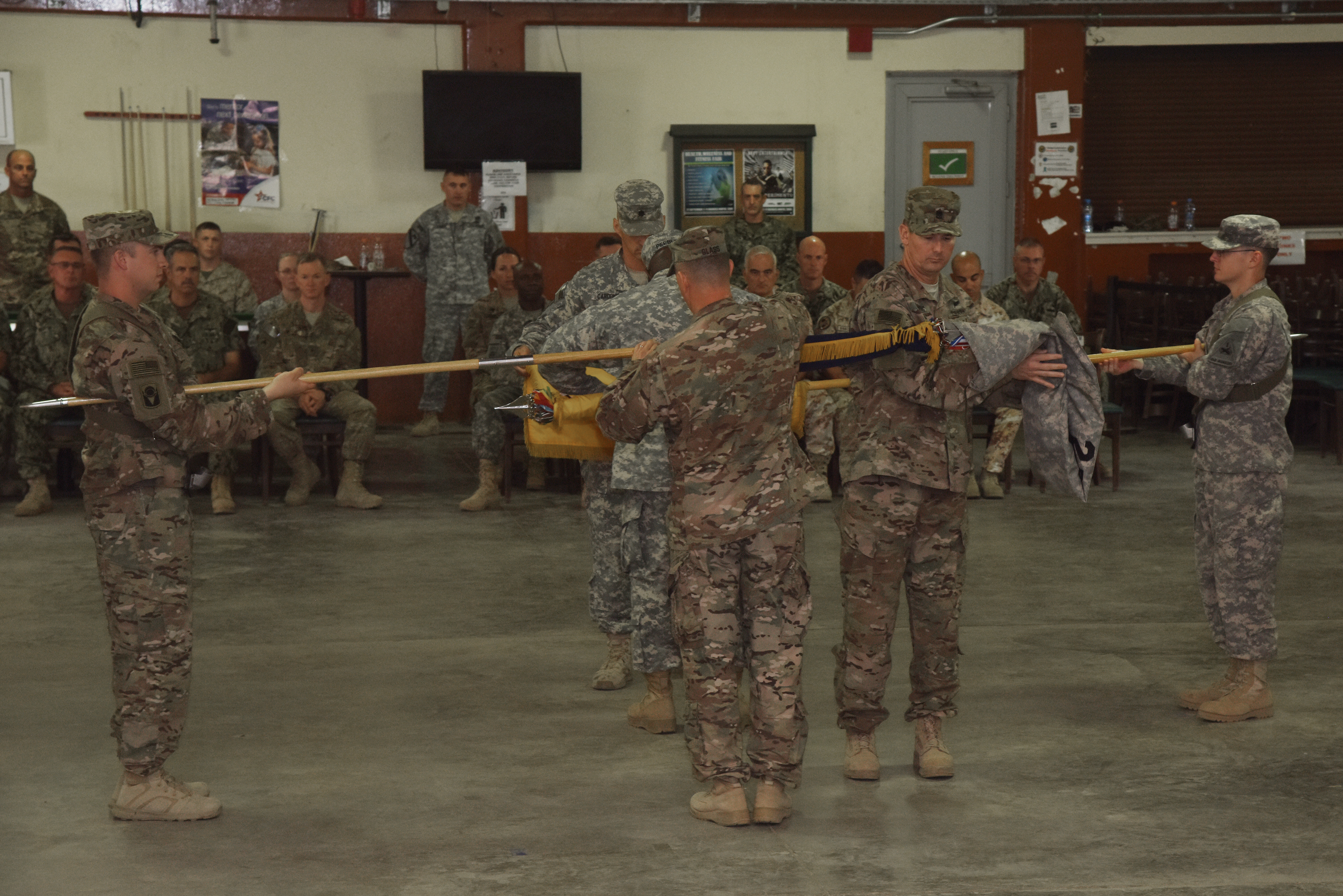 1st Battalion, 77th Armor Regiment flag is rolled, and the 2nd BN, 124th Infantry Regiment flag is unrolled during a transfer of authority ceremony at Camp Lemonnier, Djibouti, Sept. 24, 2015.  The regimental colors are a physical symbol of a unit's pride.  The casing of the 1st BN, 77th AR colors signify it's mission completion, while the uncasing of the 2nd BN, 124th IR colors signifies its preparedness to assume its role within Combined Joint Task Force-Horn of Africa.  (U.S. Air Force photo by Staff Sgt. Maria Bowman)