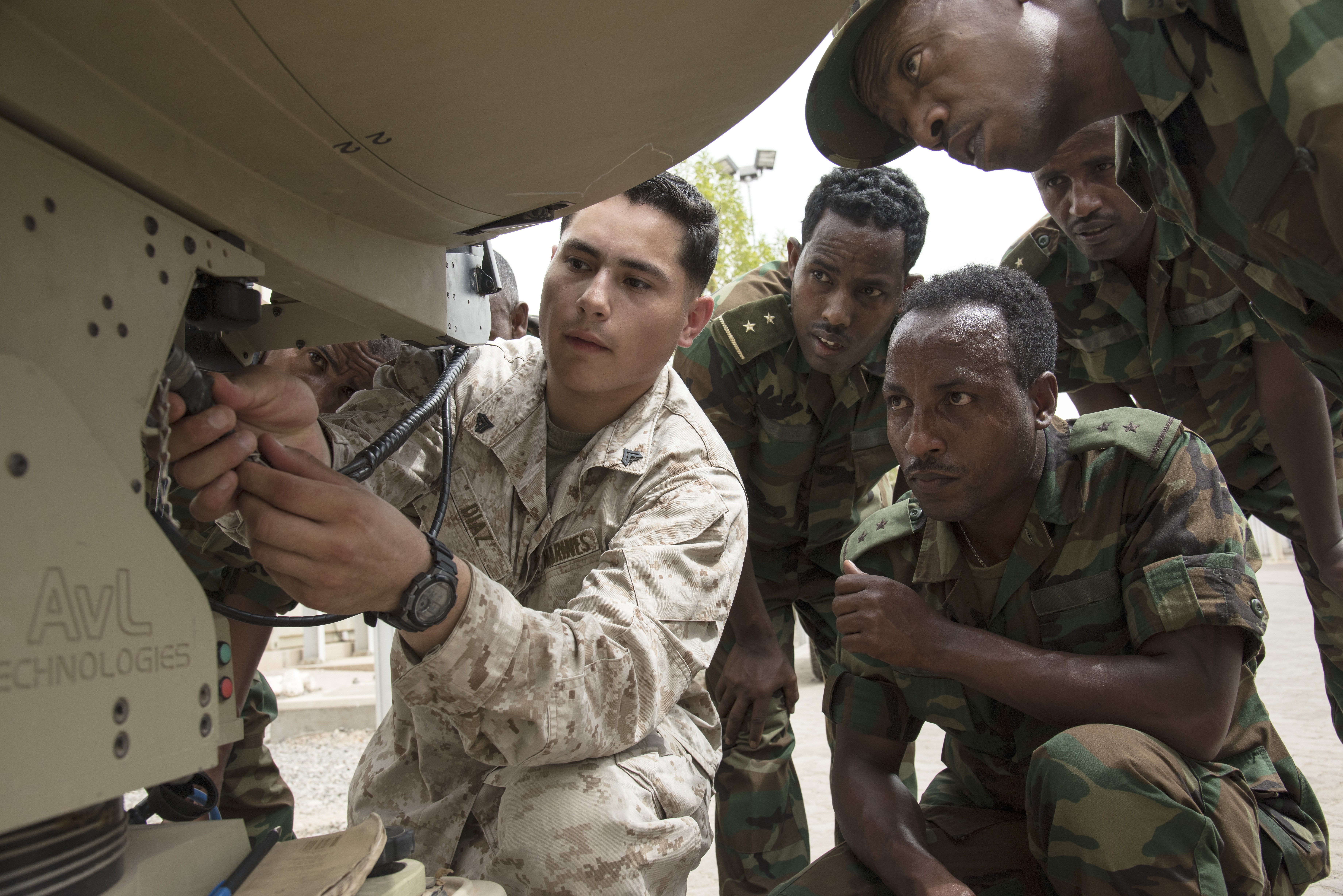 U.S. Marine Cpl. Daniel Diaz, U.S. Africa Command Data Sharing Network (ADSN) course instructor, shows intelligence specialists from the Ethiopian National Defense Force (ENDF), how to properly setup a portable communication terminal at Camp Lemonnier, Djibouti, Aug. 18, 2015. Members of the ENDF and Djiboutian Armed Forces (FAD) participated in a multi-week ADSN course, which was hosted by Combined Joint Task Force-Horn of Africa communications and intelligence personnel, and was designed to broaden communication interoperability between host nation security forces. (U.S. Air Force photo by Staff Sgt. Nathan Maysonet/released)