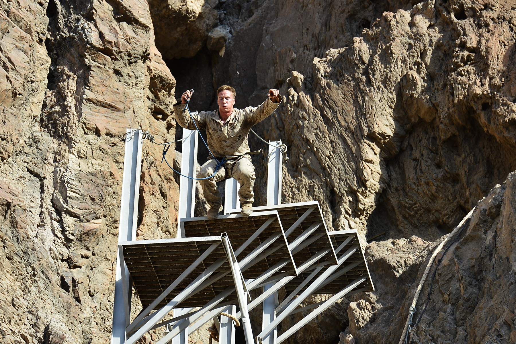 "A U.S. Marine, assigned to the 15th Marine Expeditionary Unit, jumps down platforms for a rope's course during the French Desert Survival Course, near Arta Beach, Djibouti, Sept. 30, 2015. U.S. Army Civil Affairs Battalion soldiers, assigned to Combined Joint Task Force-Horn of Africa, French Army soldiers from the 5th Overseas Combined Arms Regiment, and members of 15th Marine Expeditionary Unit, complete the ""Path of the Unconscious,"" a ropes course carved out of an approximately 300 foot high cliff. (U.S. Air Force photo by Senior Airman Nesha Humes)"