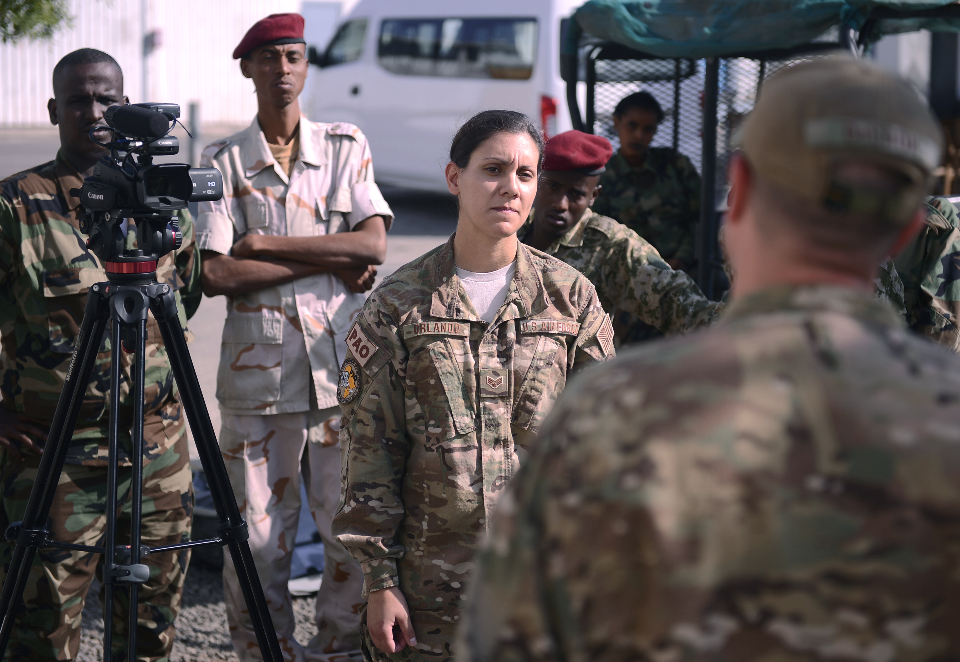 Senior Airman Nina Orlando, Combined Joint Task Force-Horn of Africa broadcast journalist, center, interviews Tech. Sgt. Daniel DeCook, photojournalism NCOIC, during a scenario Dec. 3, 2015, at Camp Lemonnier, Djibouti. Combined Joint Task Force-Horn of Africa public affairs personnel shared U.S. techniques for shooting video, operating the camera and conducting a live interview to help improve the FAD's public affairs capabilities. (U.S. Air Force photo by Senior Airman Peter Thompson)