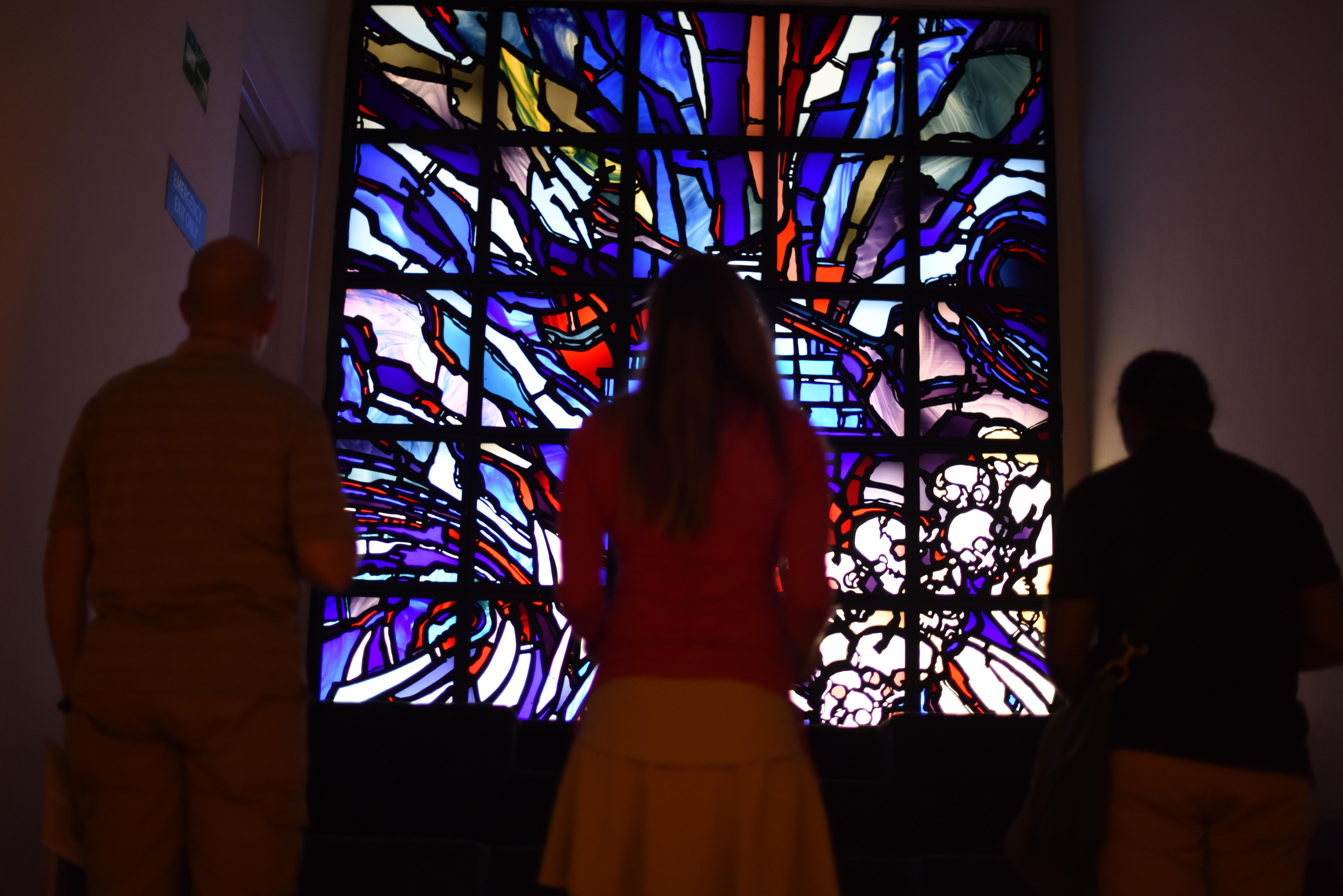 U.S. Navy Lt. Steven Hunt, U.S. Marine Corps Maj. Bevin Keen, and Navy Senior Chief Cheryl Norris contemplate a stained glass art installation at the Genocide Memorial Museum in Kigali, Rwanda, Dec. 16, 2015. While on a mission to Rwanda, representatives from Combined Joint Task Force–Horn of Africa visited the museum to learn more about the 1994 genocide and to pay respects at the museum's mass grave site where 250,000 victims were relocated after the atrocities. (U.S. Air Force photo by Staff Sgt. Victoria Sneed)