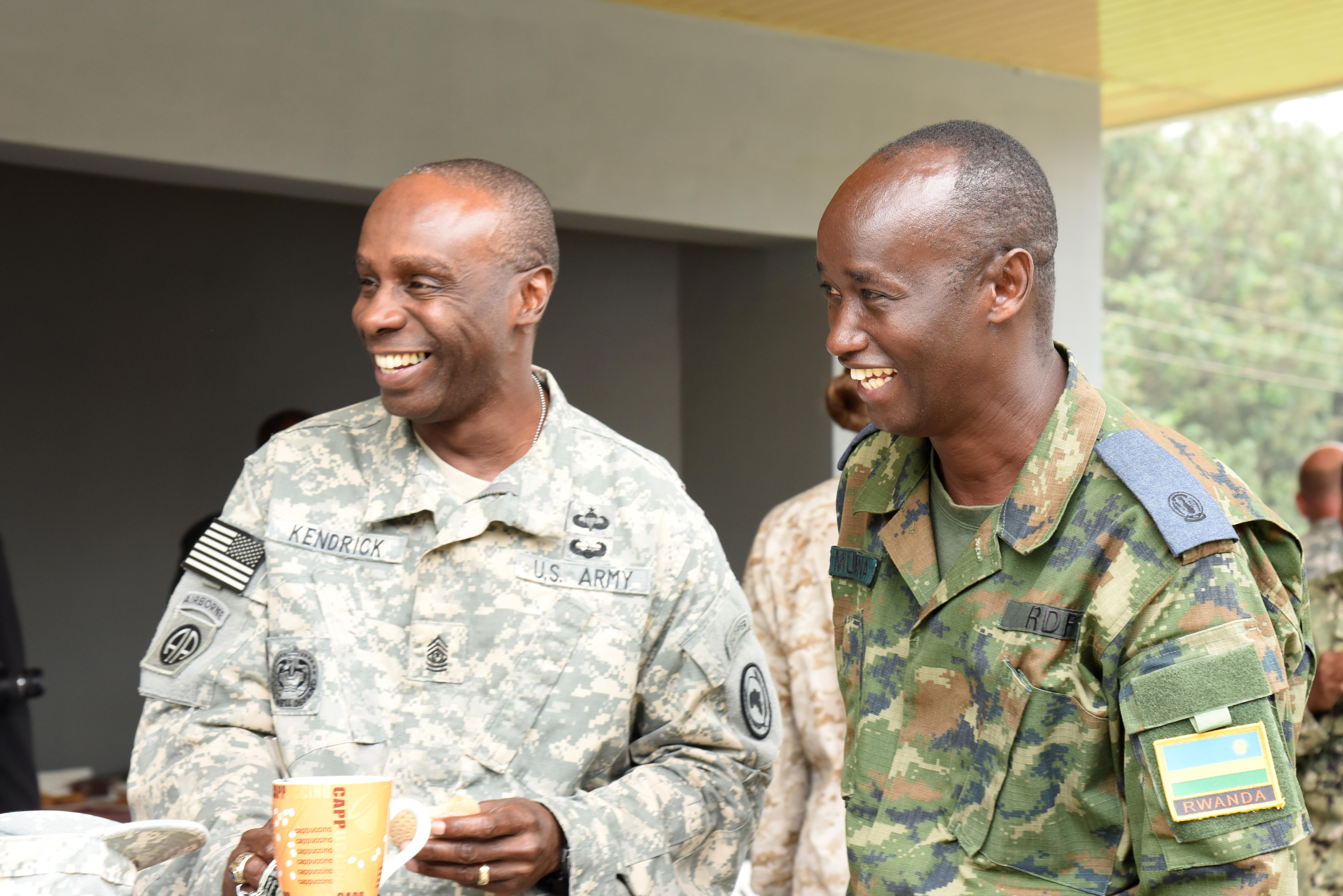 U.S. Army Command Sgt. Maj. Butler Kendrick, Combined Joint Task Force-Horn of Africa senior enlisted leader, shares a laugh with Rwandan Defense Force Air Force Maj. Jean Paul Munana, Combat Battalion squadron commander, at the RDF Engineering Brigade Headquarters near Kigali, Rwanda, Dec. 15, 2015. CJTF-HOA members socialized with RDF members during a tea break from base camp planning instruction. (U.S. Air Force photo by Staff Sgt. Victoria Sneed)