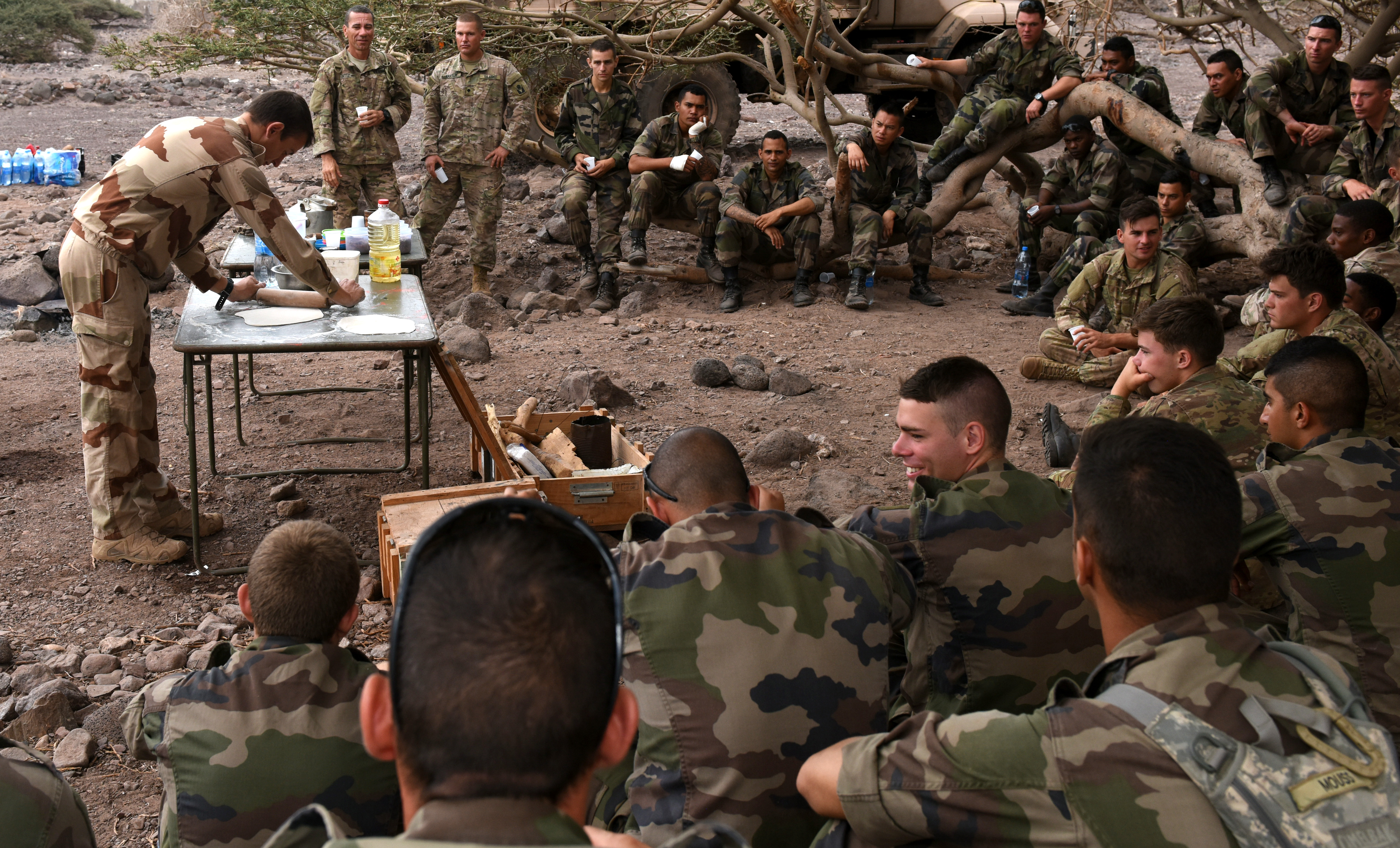 A French army survival instructor teaches French and U.S. soldiers how to make flatbread during a French Desert Survival Course near Arta Beach, Djibouti, Jan. 13, 2016.  Trainees learned how to use the resources available in a desert-like environment to prepare food and survive.  (U.S. Air Force photo by Staff Sgt. Kate Thornton)