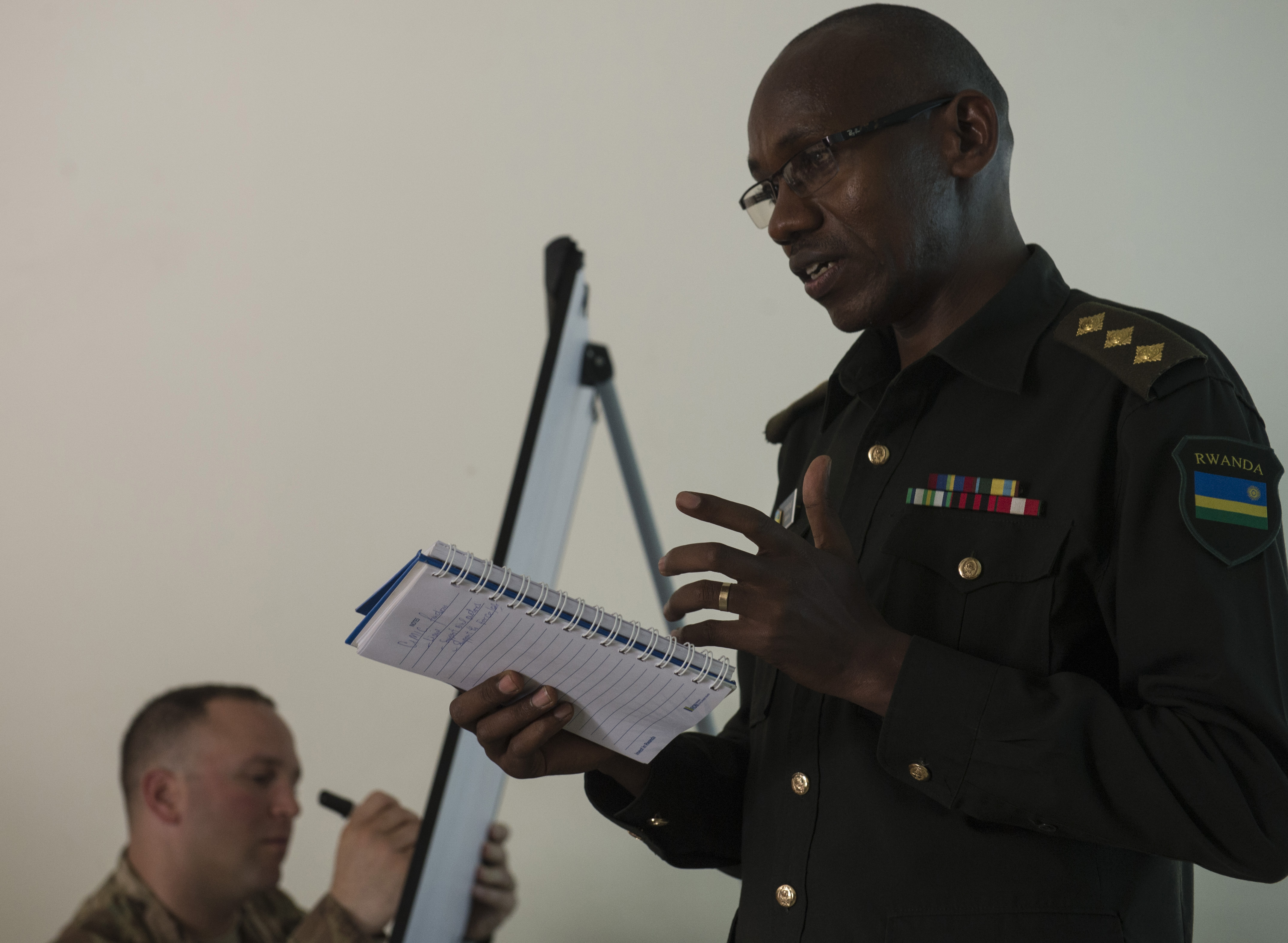 Rwanda Defense Force Army Capt. Edouard Turatsinze, Ministry of Defense Public Relations and Communications officer, reads from a list of essential tasks for Civil-Military Cooperation officers Feb. 3, 2016, at Rwanda Defense Force headquarters, Kigali, Rwanda. During conversations and breakout sessions the civil affairs and RDF explored the use of essential tasks and supporting tasks as means of identifying needed skills for proficient CIMIC personnel prior to peacekeeping and regional security organization deployments. (U.S. Air Force photo by Senior Airman Peter Thompson)