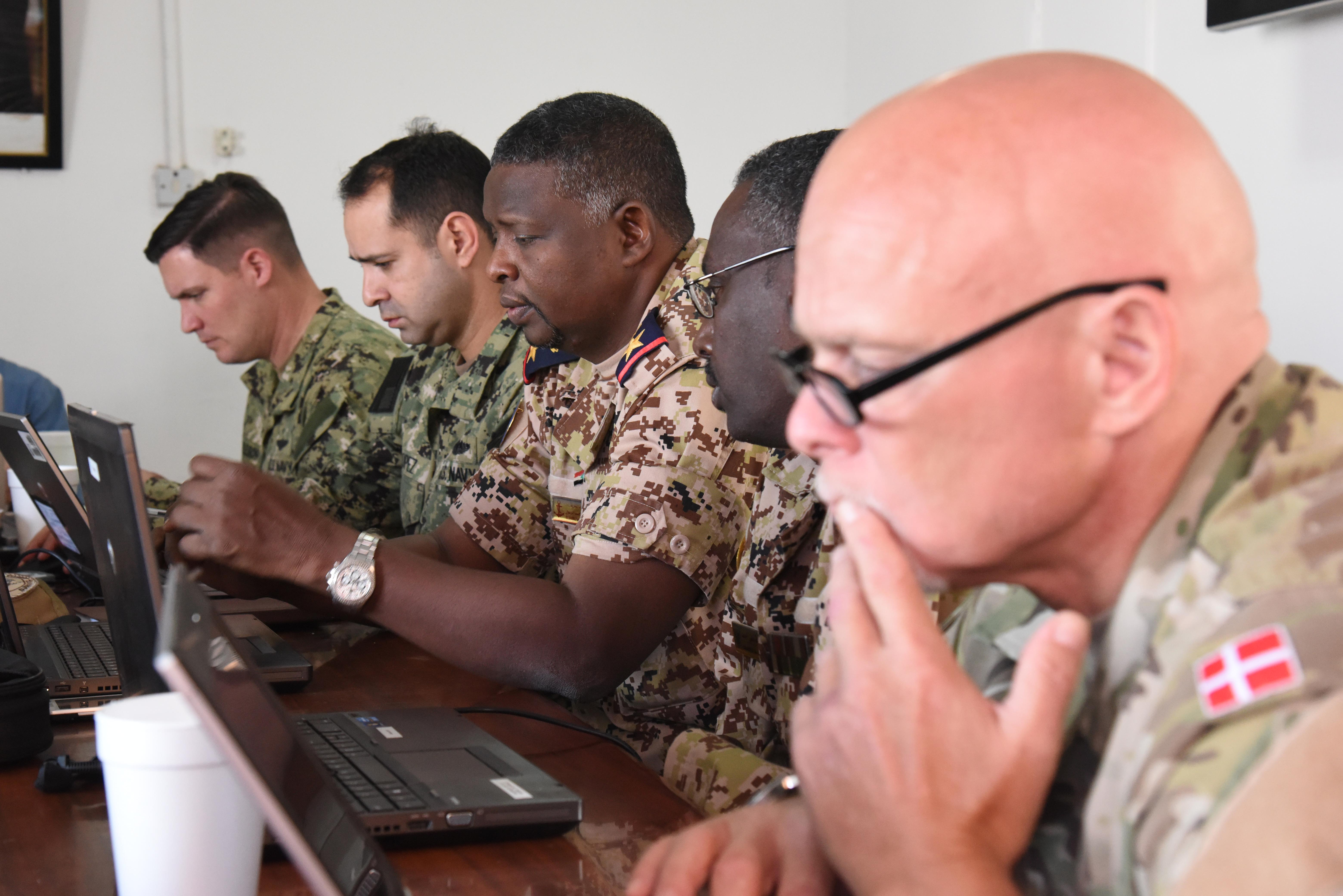 U.S., Sudan and Denmark Navy members follow the progression of scenarios from the exercise control group during Cutlass Express 2016 at the Port of Djibouti, Feb. 4, 2016. Exercise Cutlass Express provides an opportunity for maritime forces from eastern African, western Indian Ocean island nations, Europe, and the U.S. to work side-by-side to better synchronize maritime security operations for potential real-world scenarios.