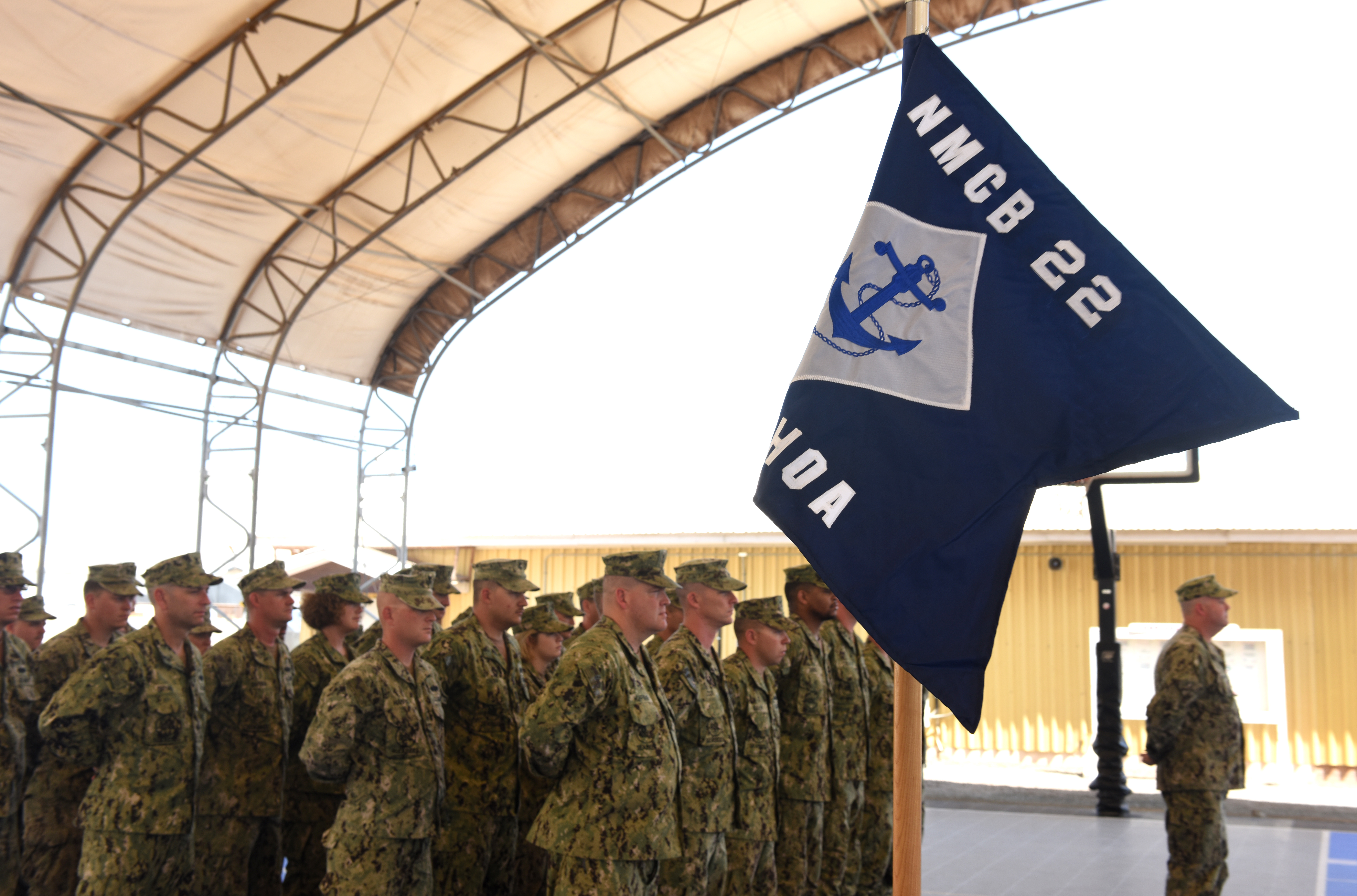 Sailors from the Naval Mobile Construction Battalion 22 attend a transfer of authority ceremony Feb. 16, 2016, at Camp Lemonnier, Djibouti. Sailors from the NMCB22 replaced the guidon at center stage signifying the transfer of authority from NMCB27, which is now preparing to redeploy home. (U.S. Air Force photo by Staff Sgt. Kate Thornton)