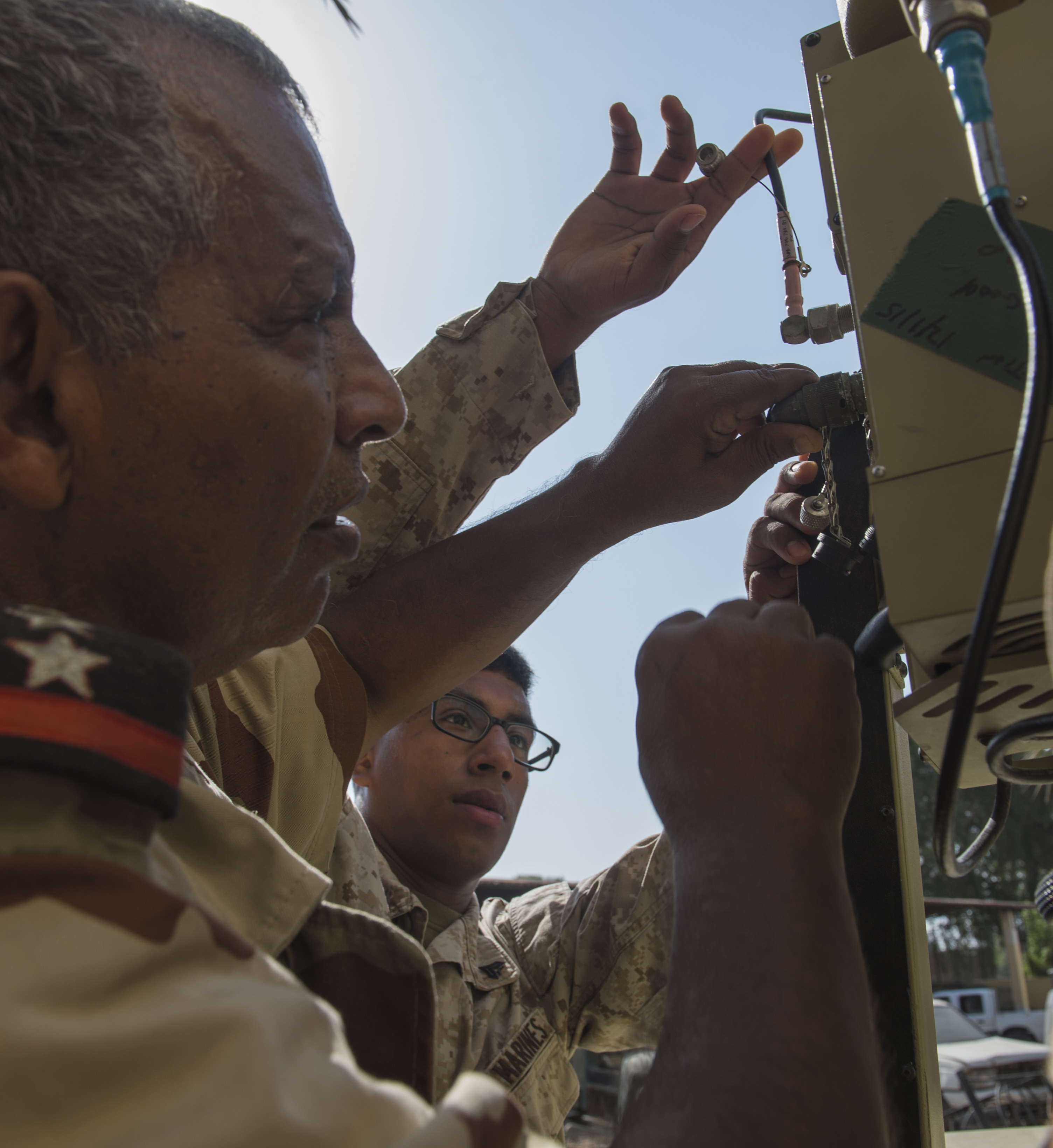 U.S. Marine Corps Cpl. Nehemias Bailon, Combined Joint Task Force-Horn of Africa, Africa Data Sharing Network (ADSN) help desk lead, helps Djiboutian Armed Forces (FAD) Capt. Amer Abdarlaziz, ADSN section chief, configure an ADSN terminal Feb. 18, 2016, in Djibouti. The ADSN is a means for African Union Mission in Somalia (AMISOM) troop contributing countries to communicate and share information with the U.S. and amongst each other. Members of CJTF-HOA taught FAD members how to install and operate a terminal, and how to access the ADSN. (U.S. Air Force photo by Senior Airman Peter Thompson)