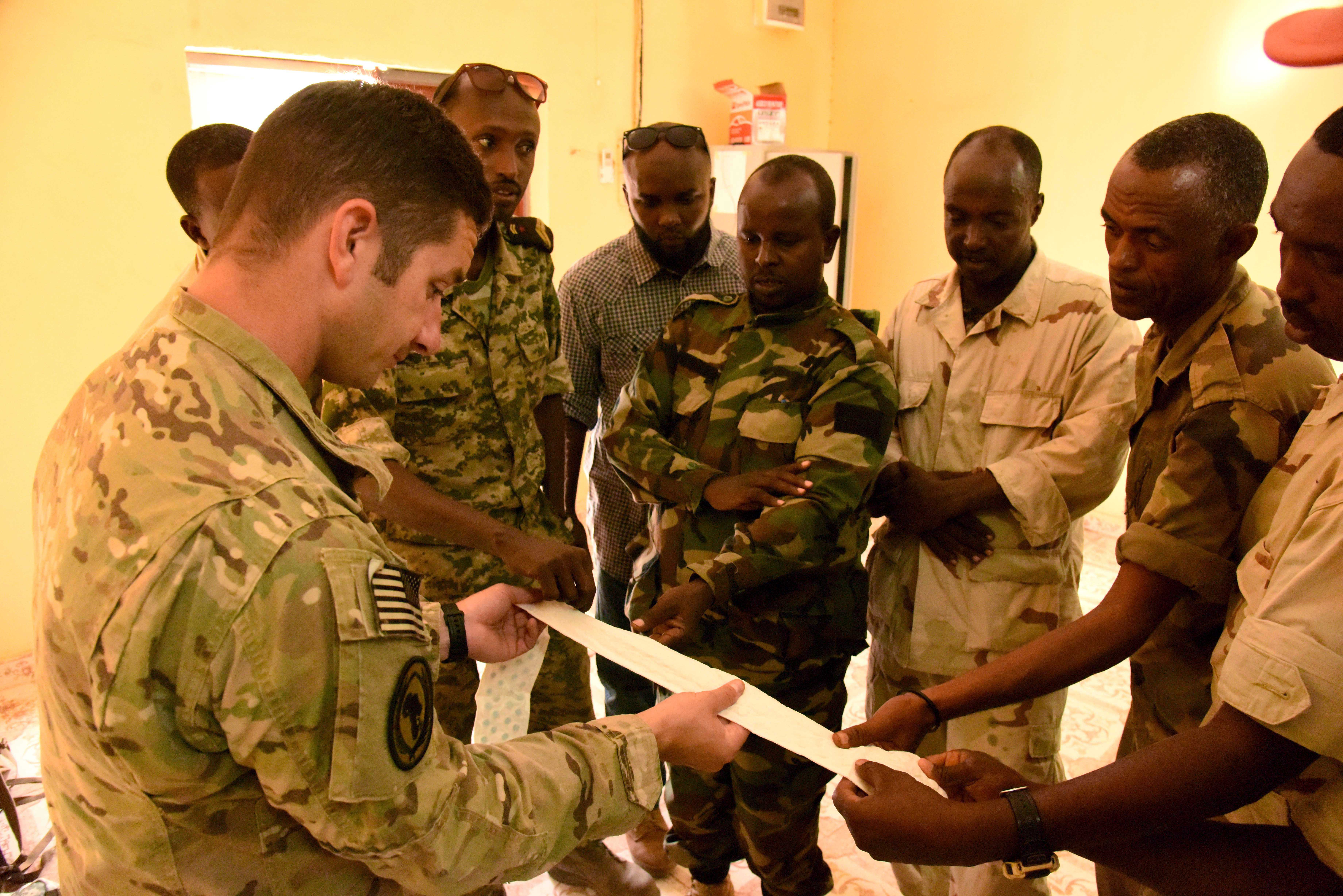 U.S. Army Sgt. Scott Winkler, 6th Squadron, 8th Cavalry Regiment combat medic, shows Djiboutian Armed Forces (FAD) soldiers bandages that have liquid absorbing pellets during a Combat Lifesaver Course at the Central Management of Materials and Engineering Services compound, Djibouti, Mar. 5, 2016. FAD soldiers learned how to diagnose, treat and transport injuries in a combat situation. (U.S. Air Force photo by Staff Sgt. Victoria Sneed)