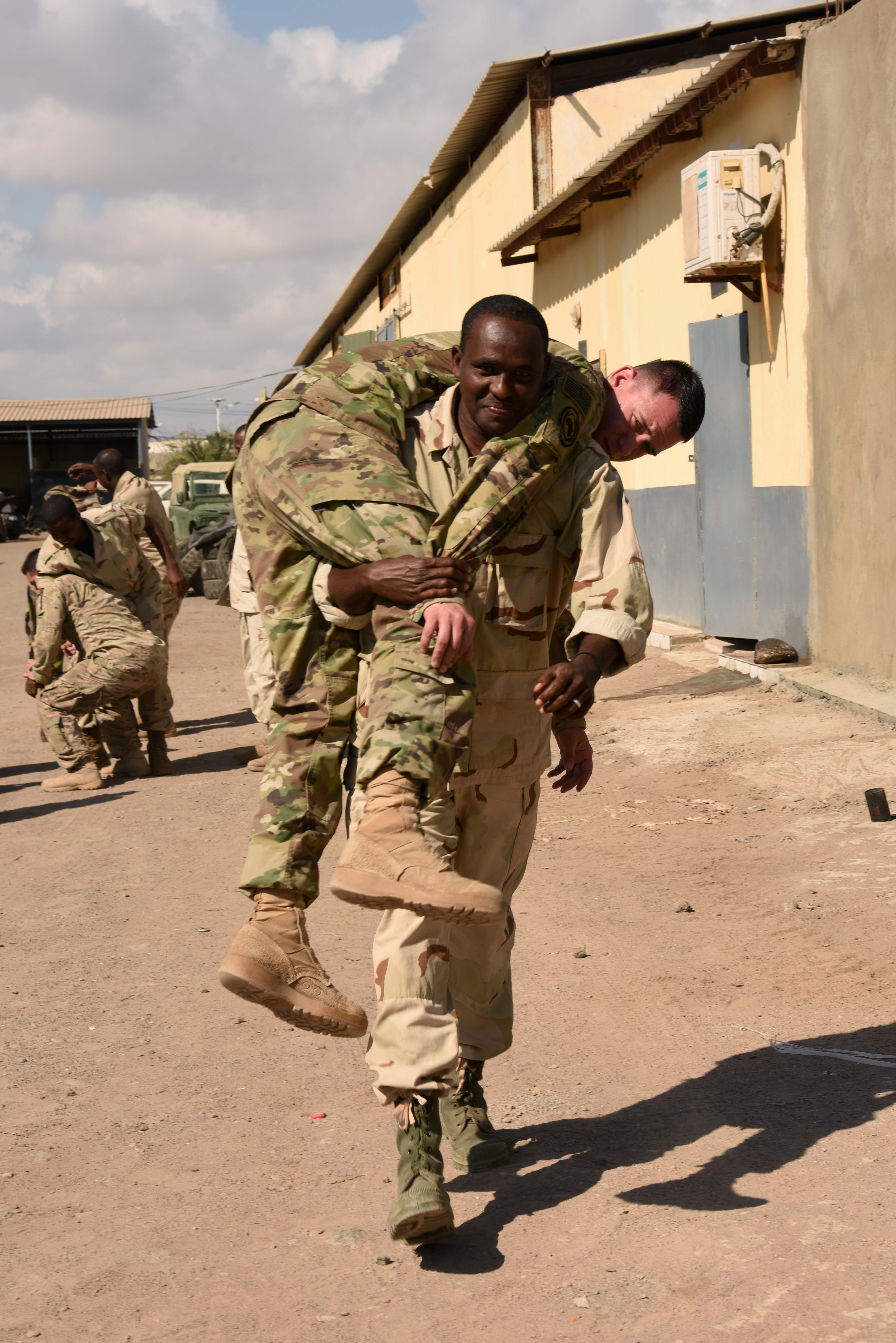 A Djiboutian Armed Forces (FAD) soldier fireman carries U.S. Army Spc. Brian Buchanan, 6th Squadron, 8th Cavalry Regiment combat medic, during a Combat Lifesaver Course at the Central Management of Materials and Engineering Services compound, Djibouti, Mar. 2, 2016. FAD soldiers learned multiple types of carries to evacuate wounded from the battlefield while also maintaining security. (U.S. Air Force photo by Staff Sgt. Victoria Sneed)