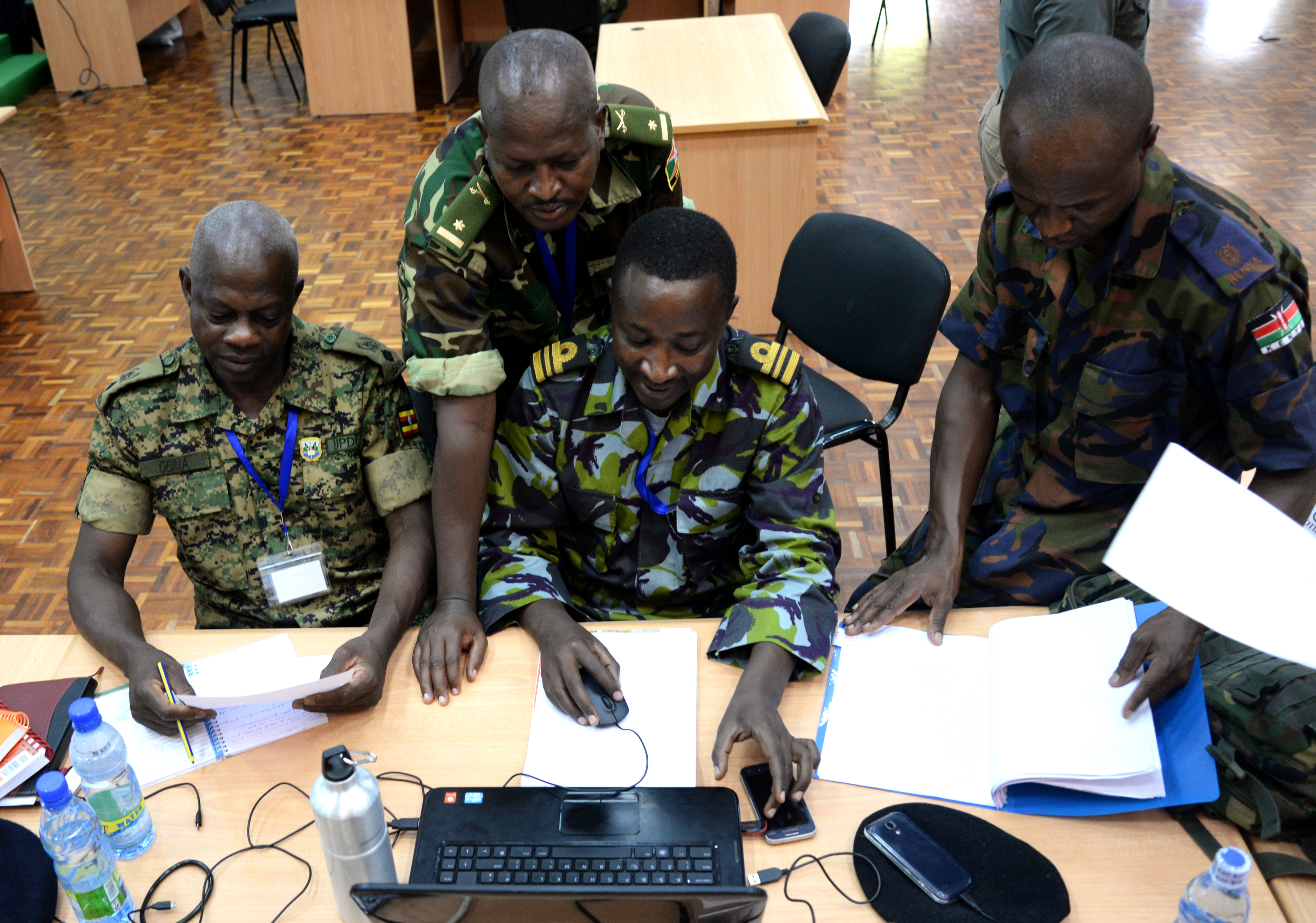 Officers from Kenya, Burundi and Uganda discuss military operations for a simulated scenario March 1, 2016, during an exercise to complete a staff officers course in Nairobi, Kenya. At the beginning of the course, the officers were split into six main directorates necessary for successful military operations: logistics and personnel, intelligence, public information, civil affairs, military operations, and command leadership. (U.S. Air Force photo by Staff Sgt. Kate Thornton)