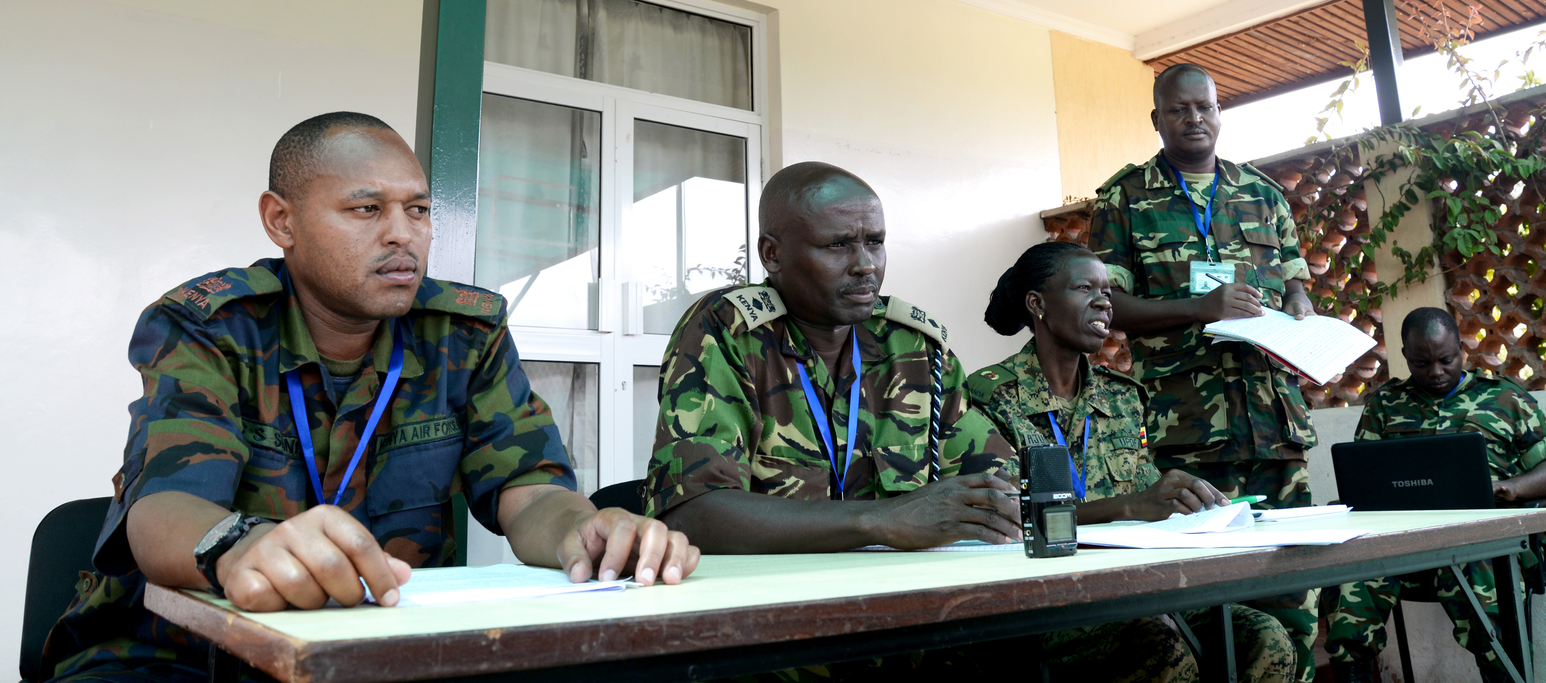 Officers from Kenya, Burundi and Uganda answer questions at a simulated press conference March 3, 2016, during an exercise to complete an AMISOM staff officers course in Nairobi, Kenya. Course mentors recorded the practice conference to show the officers their performance and ultimately lead to improvement. (U.S. Air Force photo by Staff Sgt. Kate Thornton)