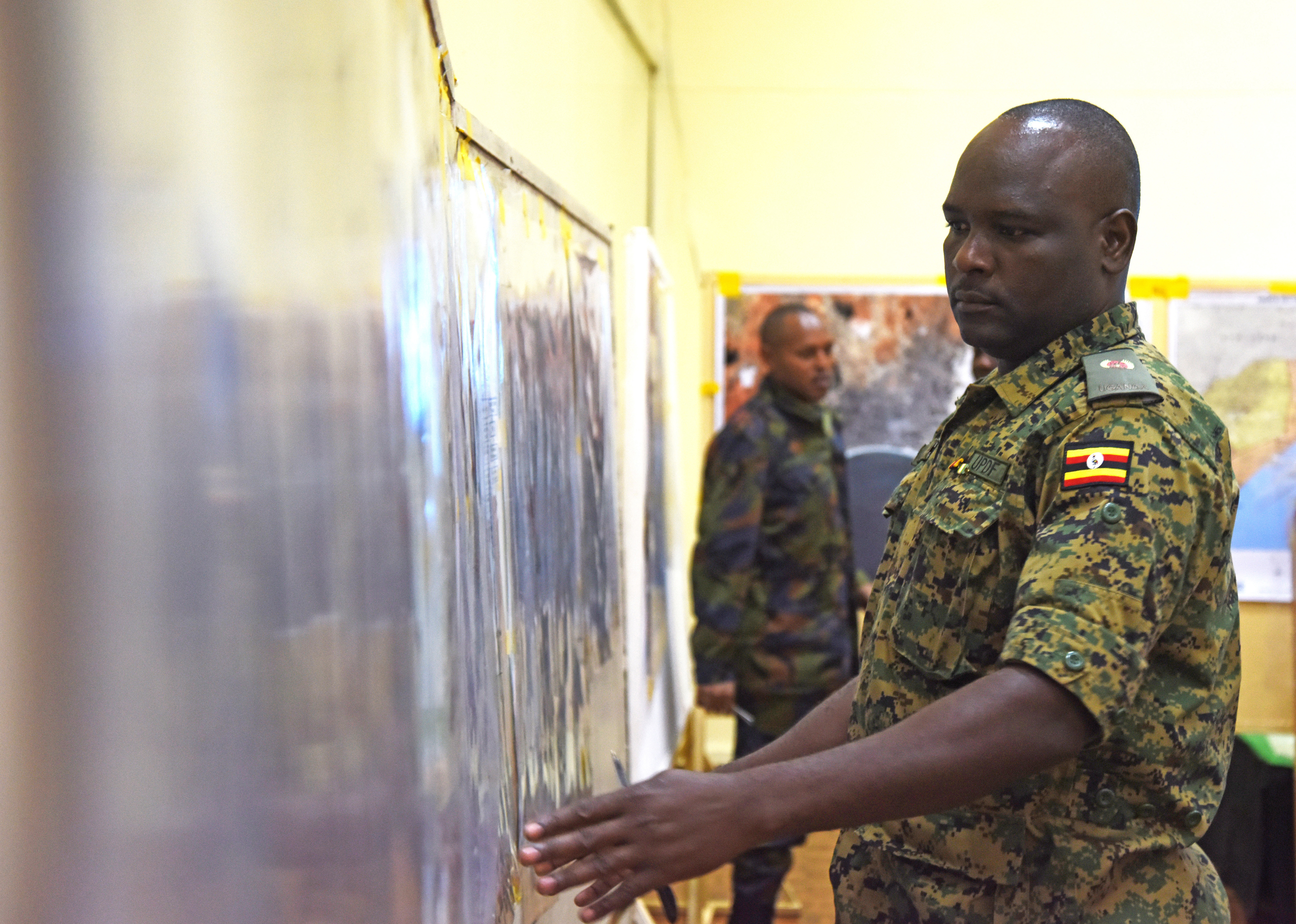 A Ugandan military officer analyzes maps prior to an exercise Feb. 29, 2016, during an African Union Mission in Somalia staff officers course in Nairobi, Kenya. The course included traditional classroom instruction, hands-on application, practical exercises, exposure to high-level military decision-making, and ended with one final exercise.  (U.S. Air Force photo by Staff Sgt. Kate Thornton)