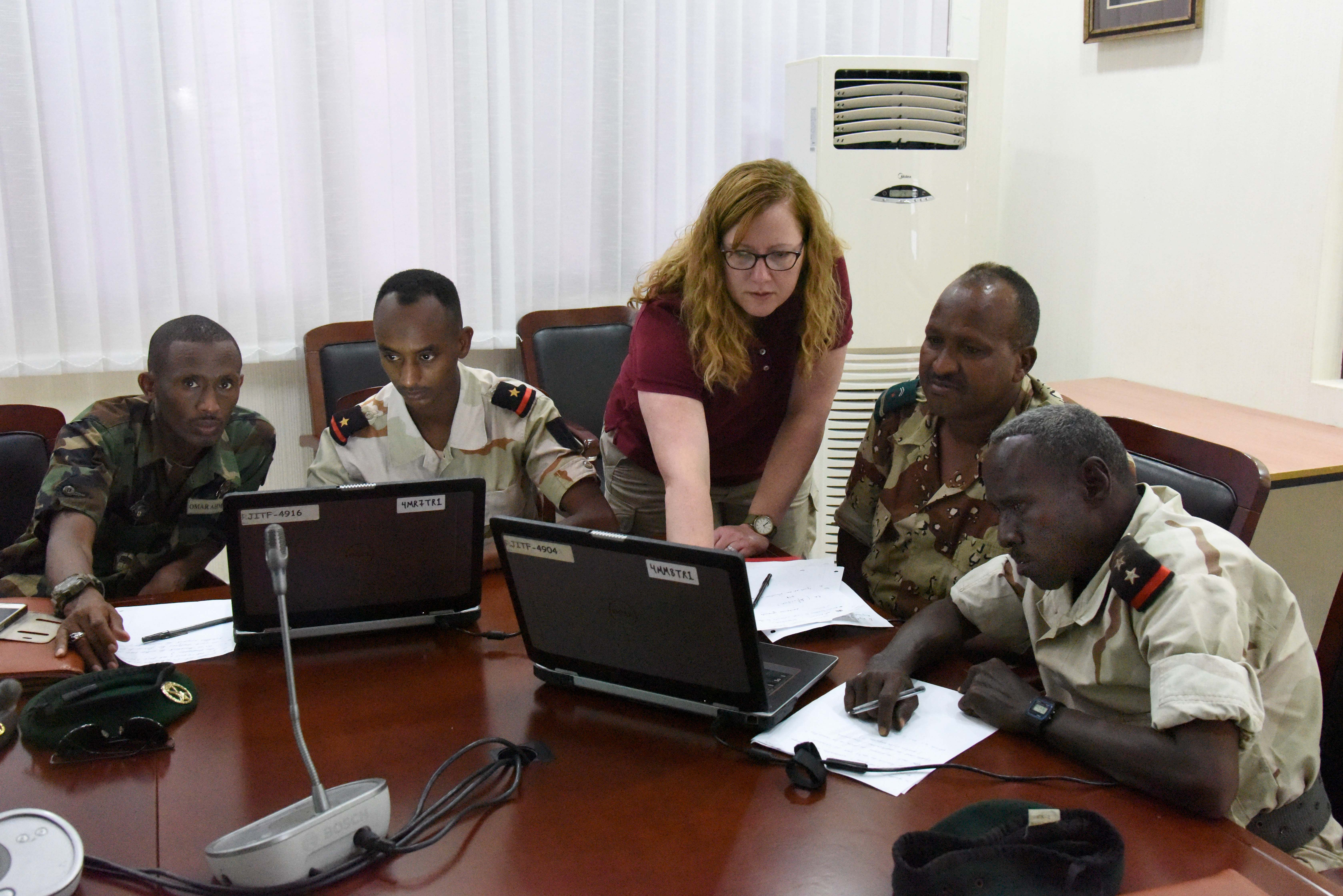 Cynthia, Regional Joint Intel Training Facility (RJITF) instructor from Royal Air Force Molesworth, U.K., points out source information to Djiboutian Armed Forces members during an open source intelligence course at the People's Palace, Djibouti, March 5-10, 2016. The course introduced students to finding different sources, how to validate those sources and risk assessments. (U.S. Air Force photo by Staff Sgt. Victoria Sneed)