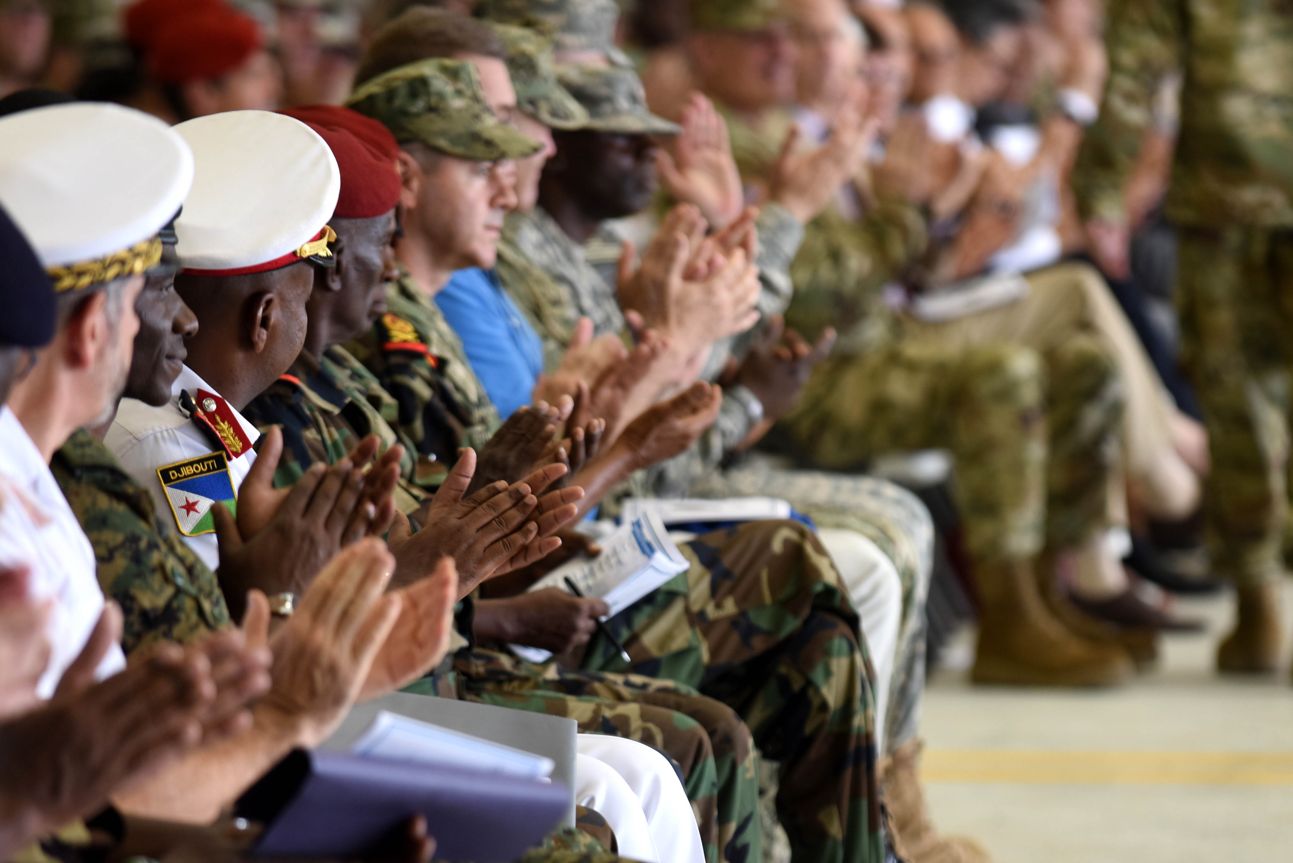 Service members, diplomats and multi-national guests applaud during a change of command ceremony April 13, 2016, at Camp Lemonnier, Djibouti. Sonntag is now in command of CJTF-HOA and responsible for its impact on the East African region. (U.S. Air Force photo by Staff Sgt. Kate Thornton)