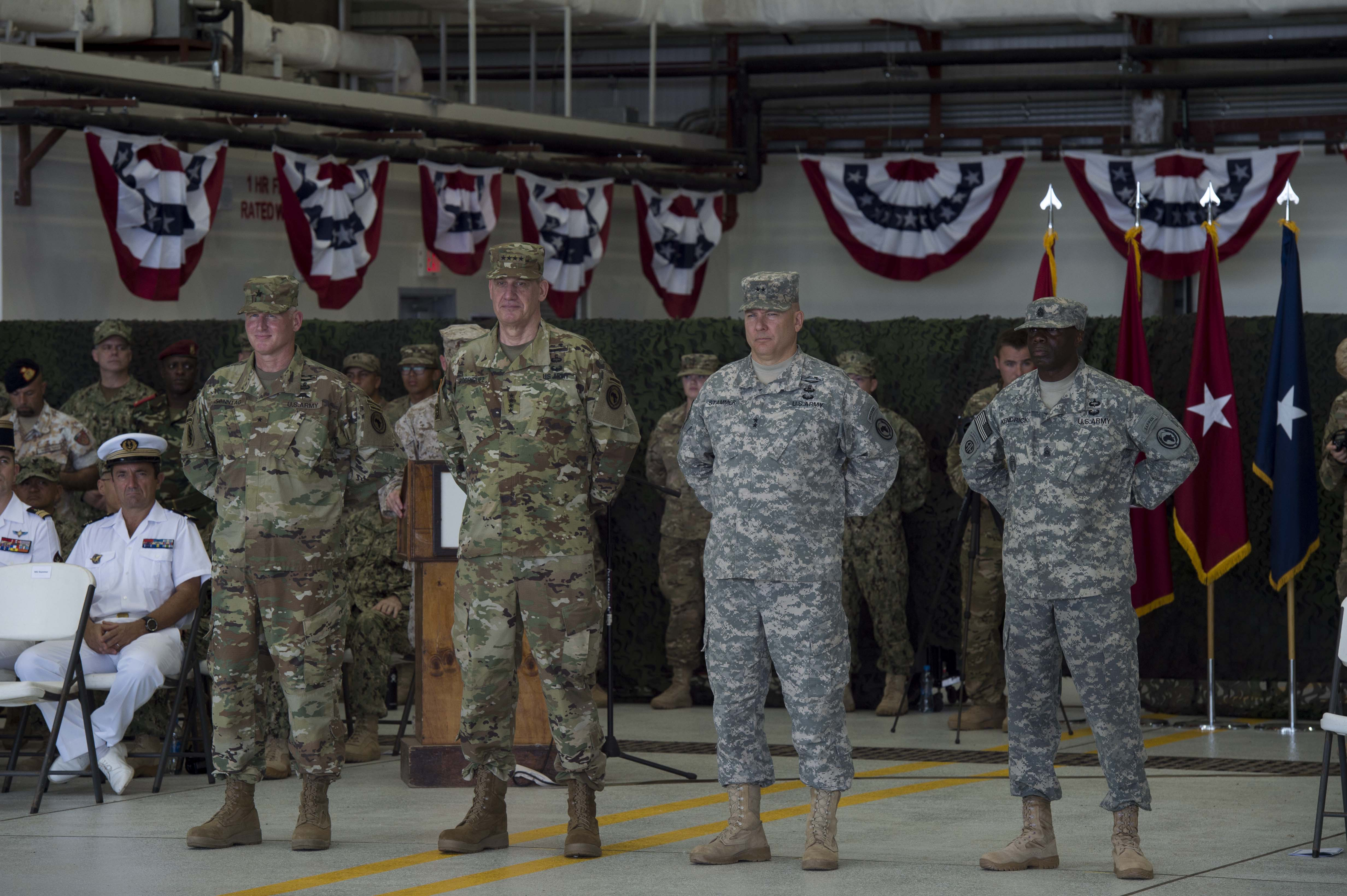Members of Combined Joint Task Force-Horn of Africa stand at attention as responsibilities of the unit are transferred to a new commander during the CJTF-HOA change of command ceremony April 13, 2016, at Camp Lemonnier, Djibouti. The ceremony also featured a transfer of responsibility during which U.S. Navy Command Master Chief Geoffrey P. Steffee assumed the role of CTJF-HOA command senior enlisted leader from U.S. Army Command Sgt. Maj Butler Kendrick Jr. (U.S. Air Force photo by Staff Sgt. Eric Summers Jr.)