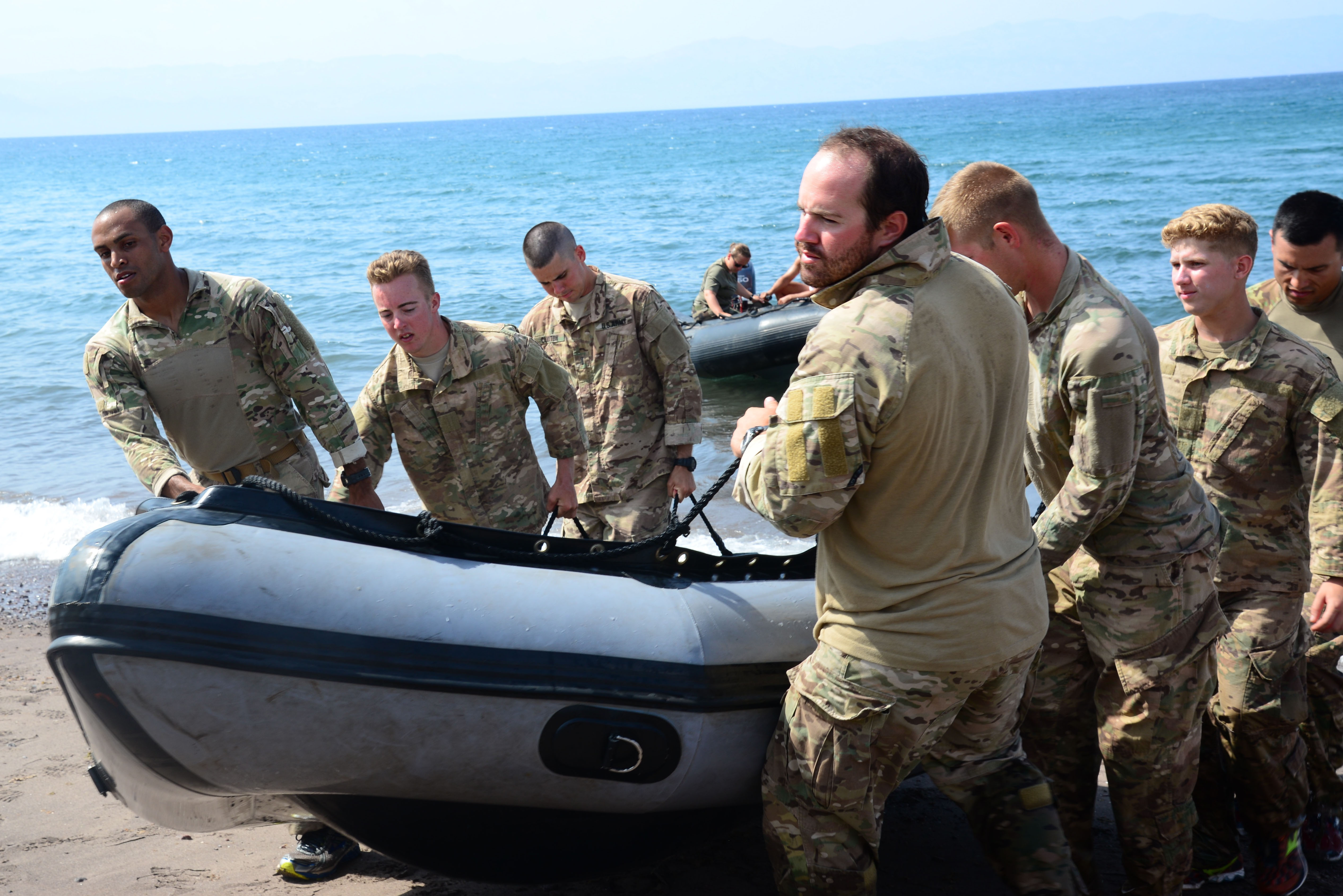 U.S. Army soldiers from the 2nd Battalion, 124th Infantry Regiment, carry a zodiac watercraft across a beach during a water crossing exercise May 5, 2016, at Arta Plage, Djibouti. The soldiers were required to run the watercraft across a beach, paddle to a drowning victim,  and run back and run back to the starting point. (U.S. Air Force photo by Senior Airman Benjamin Raughton/Released)