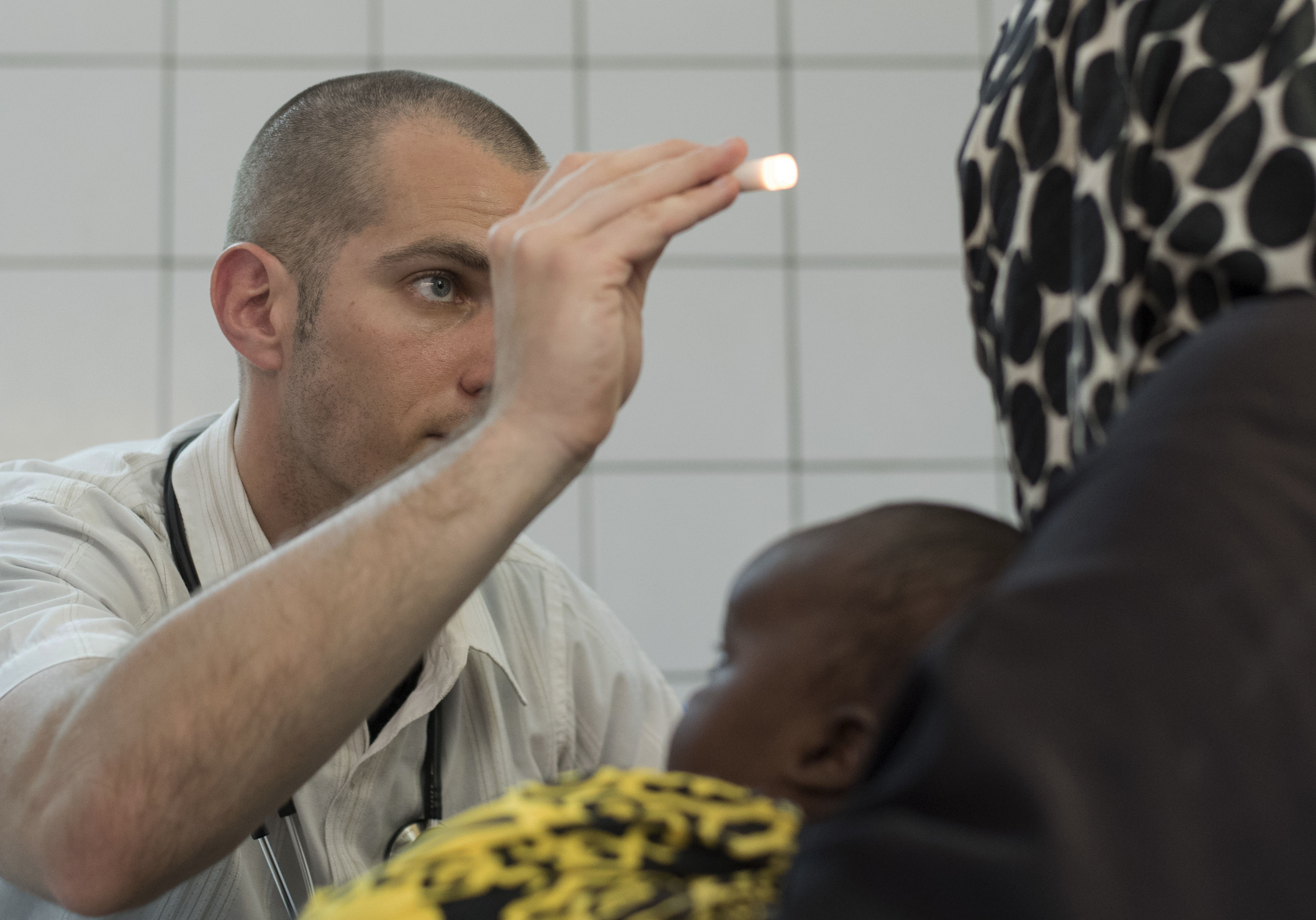 DIKHIL, Djibouti – U.S. Army Maj. Andrew Mosier, 403rd Civil Affairs Battalion medical cell chief medical officer, conducts a health assessment on a Dikhil woman during a two-day medical civic action program at Dikhil, Djibouti, May 11, 2016. The 403rd CA BN partnered with Djibouti Ministry of Health and Cuban medical personnel to provide medical care and treatment to approximately 140 patients while exchanging medical knowledge. (U.S. Air Force photo by Staff Sgt. Tiffany DeNault)
