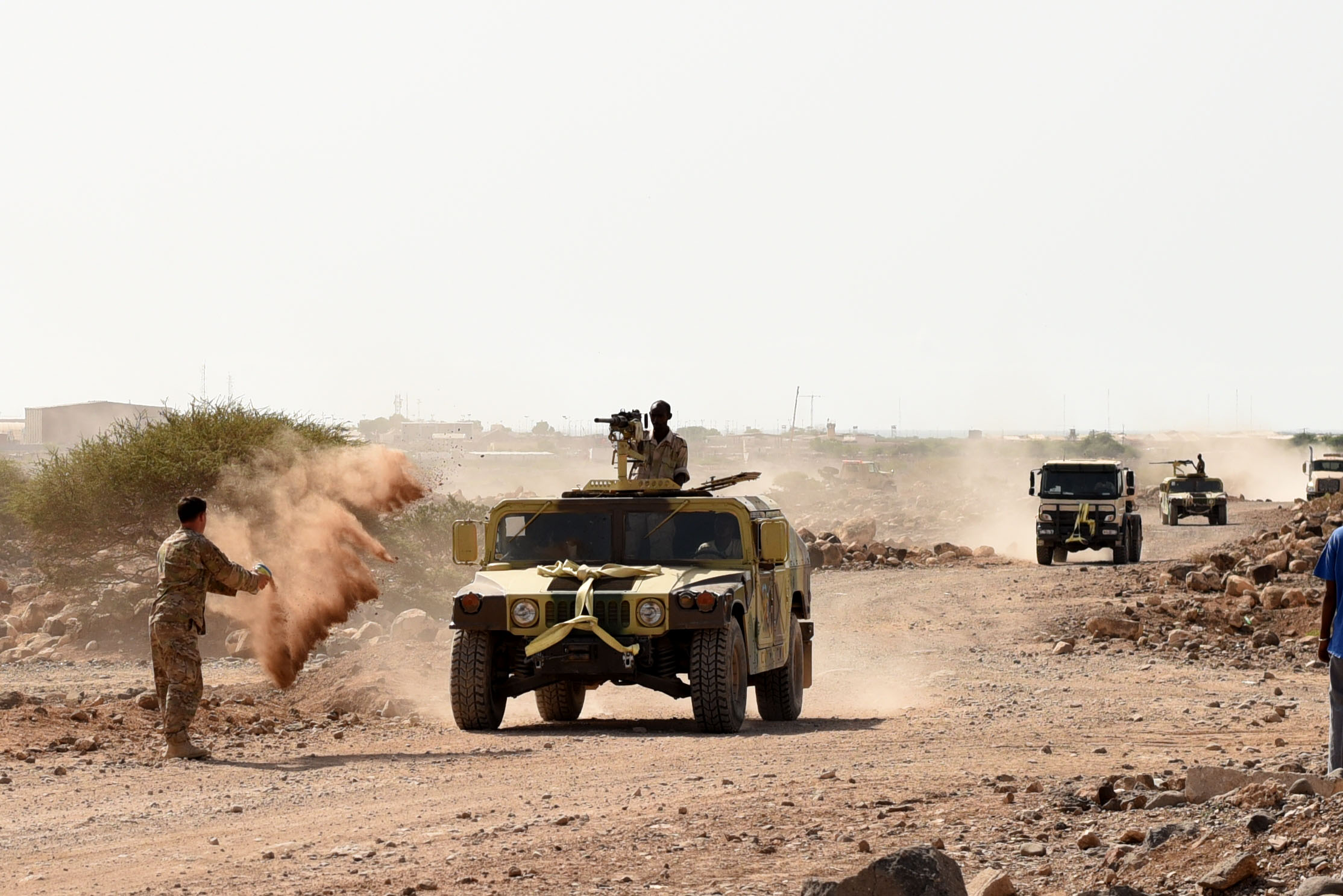 CAMP CHEIK OSMAN, Djibouti – U.S. Army Sgt. Robert Shelton, U.S. Army Regionally Aligned Forces instructor, throws dirt at a Humvee to simulate a roadside detonation causing immobility during Area Logistics Training final with Djiboutian Armed Forces (FAD) soldiers, May 16, 2016, at Camp Cheik Osman, Djibouti. The FAD soldiers tested combat skills they learned throughout the five month course demonstrating their reactions to various mock situations from convoying through a road block, identifying mock roadside bombs, medical care, and vehicle recovery. (U.S. Air Force photo by Staff Sgt. Tiffany DeNault)