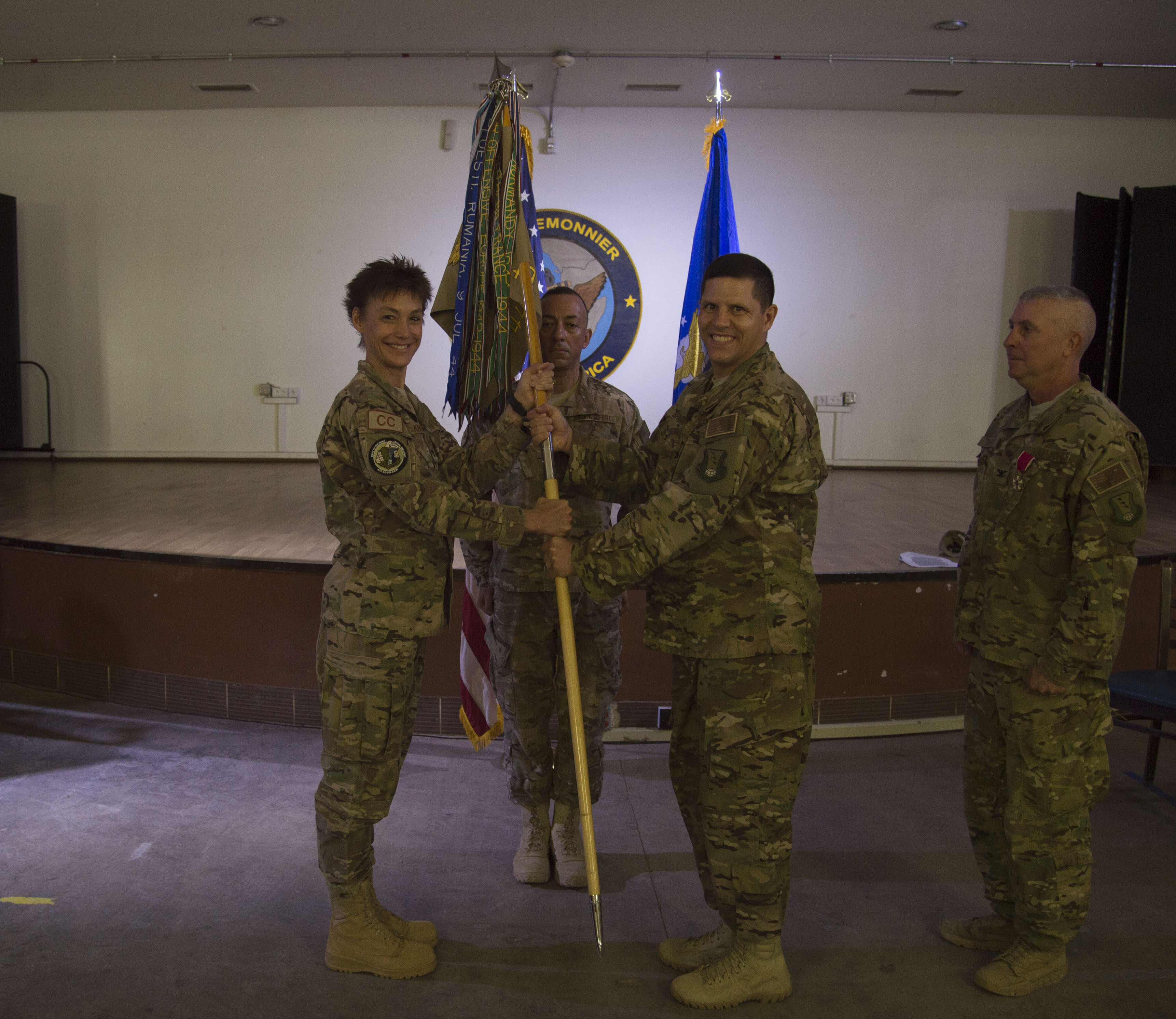 U.S. Air Force Col. Michael Bruzzini, 449th Air Expeditionary Group incoming commander, receives the 449th AEG flag from U.S. Air Force Col. Andra Kniep, 435th Air Expeditionary Wing commander, during the 449th AEG Change of Command ceremony June 6, 2016, at Camp Lemonnier, Djibouti. The passing of the flag is a military tradition signifying the change of authority and responsibility of a unit from one commander to another. (U.S. Air Force photo by Staff Sgt. Eric Summers Jr.)