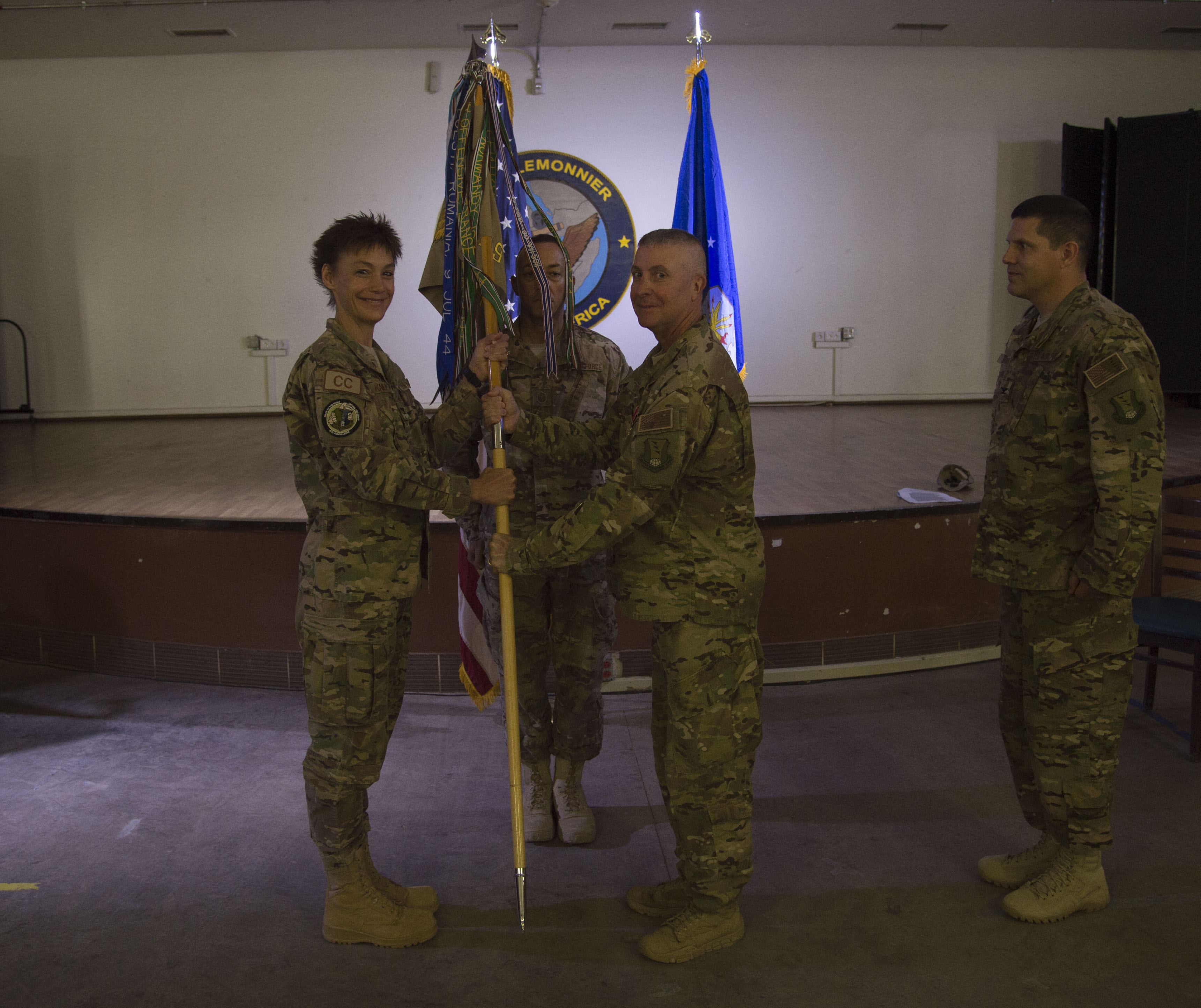 U.S. Air Force Col. Daniel Duffy, 449th Air Expeditionary Group outgoing commander, hands the 449th AEG flag to U.S. Air Force Col. Andra Kniep, 435th Air Expeditionary Wing commander, during the 449th Change of Command ceremony June 6, 2016, at Camp Lemonnier, Djibouti. The passing of the flag is a military tradition signifying the change of authority and responsibility of a unit from one commander to another. (U.S. Air Force photo by Staff Sgt. Eric Summers Jr.)