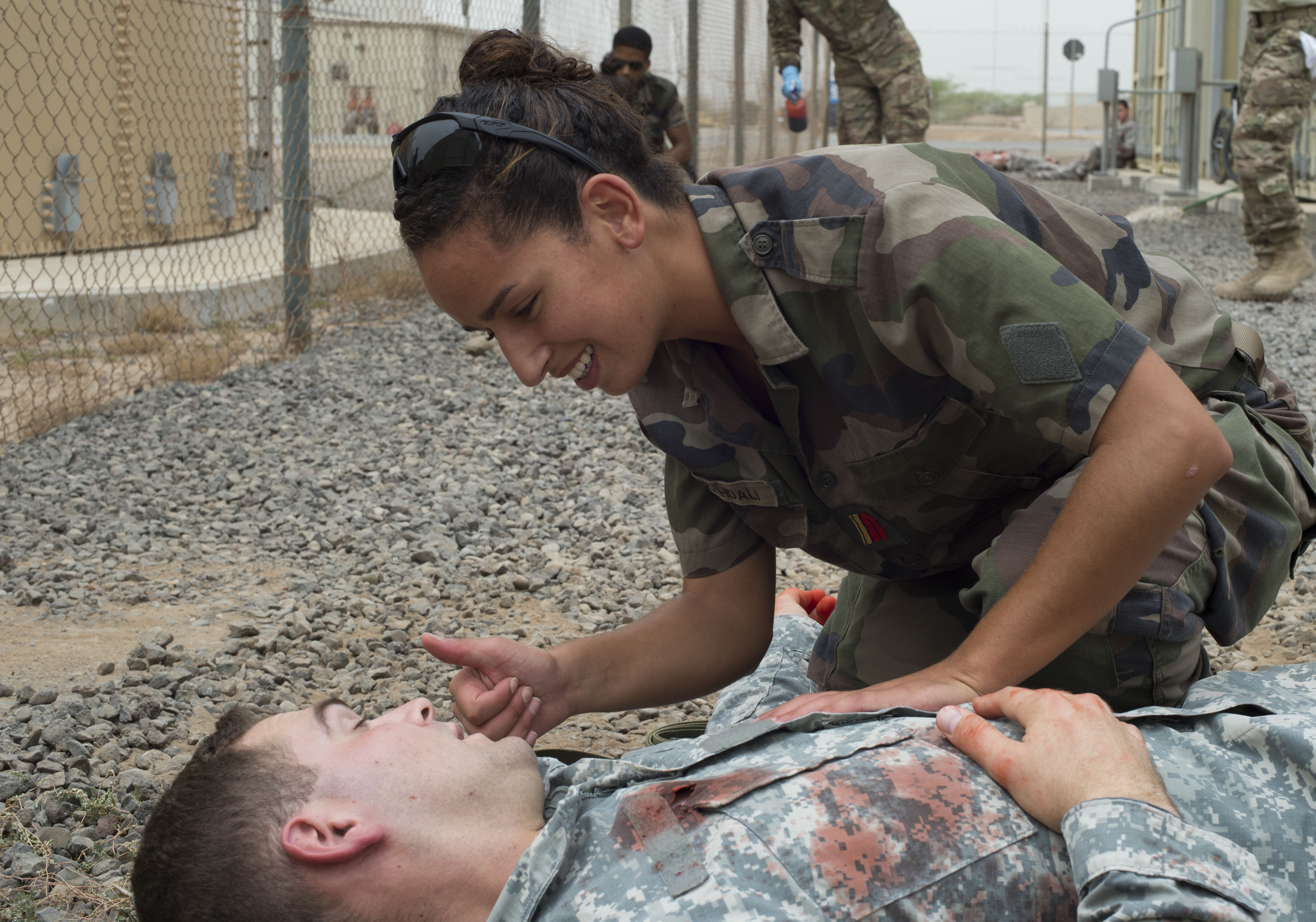 Caporal-chef Adjudant, a French military medical officer, uses hand gestures to communicate with a simulated casualty during a combat lifesaver course practical exam June 23, 2016, at Camp Lemonnier, Djibouti. The French participants brought their own medical supplies to show how they treat patients. (U.S. Air Force photo by Staff Sgt. Eric Summers Jr.)w
