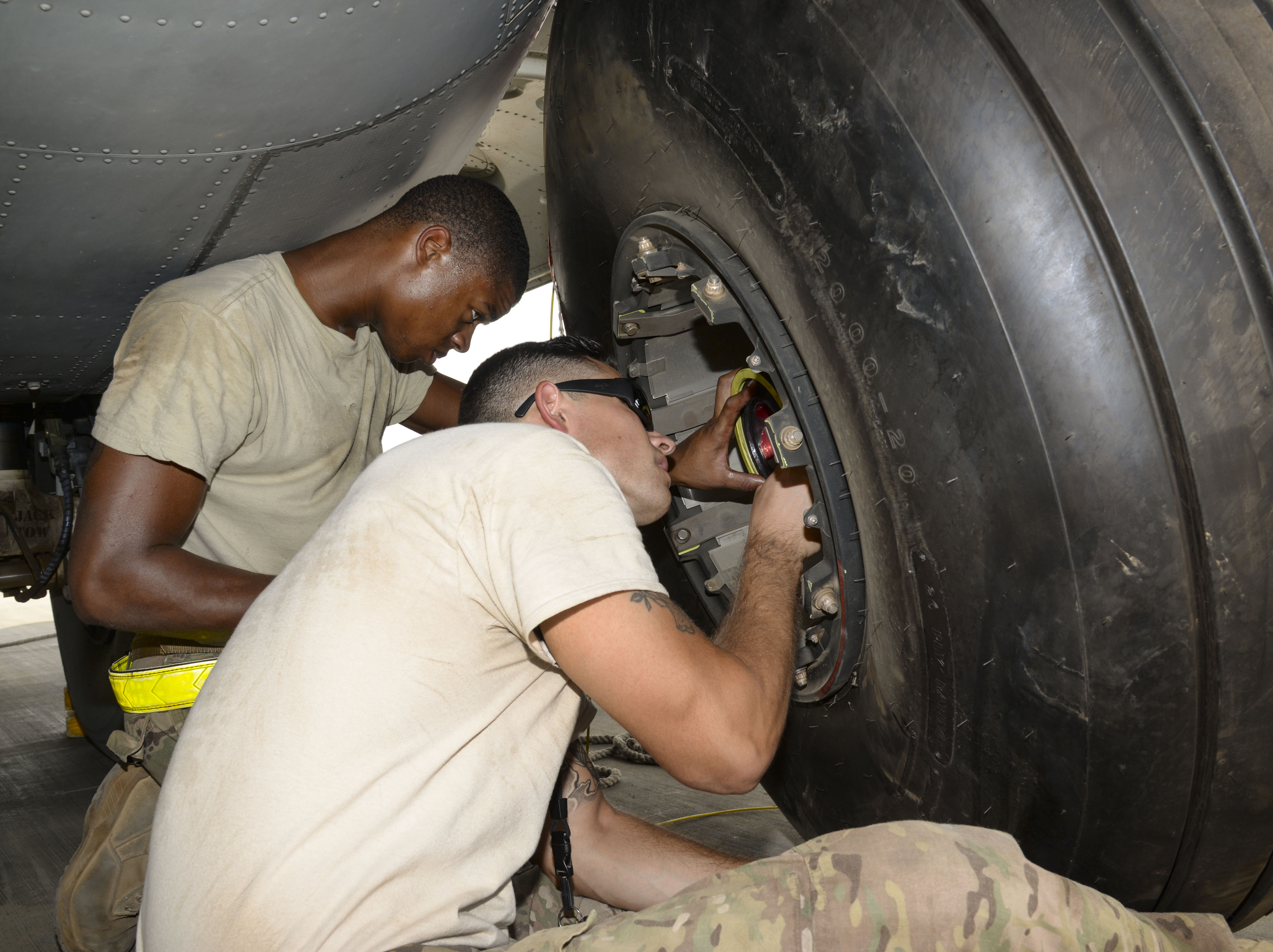 Senior Airman Tavaris Scott, 81st Expeditionary Rescue Squadron crew chief, left, and Staff Sgt. Michael Patterson, 81st ERQS aerospace propulsion craftsman, team up to change a tire on a C-130J Hercules main landing gear at Camp Lemonnier, Djibouti, July 18, 2016. The C-130J underwent routine maintenance to continue the mission of personnel recovery and protect and defend United States interests in Eastern Africa. (U.S. Air Force photo by Staff Sgt. Benjamin Raughton)