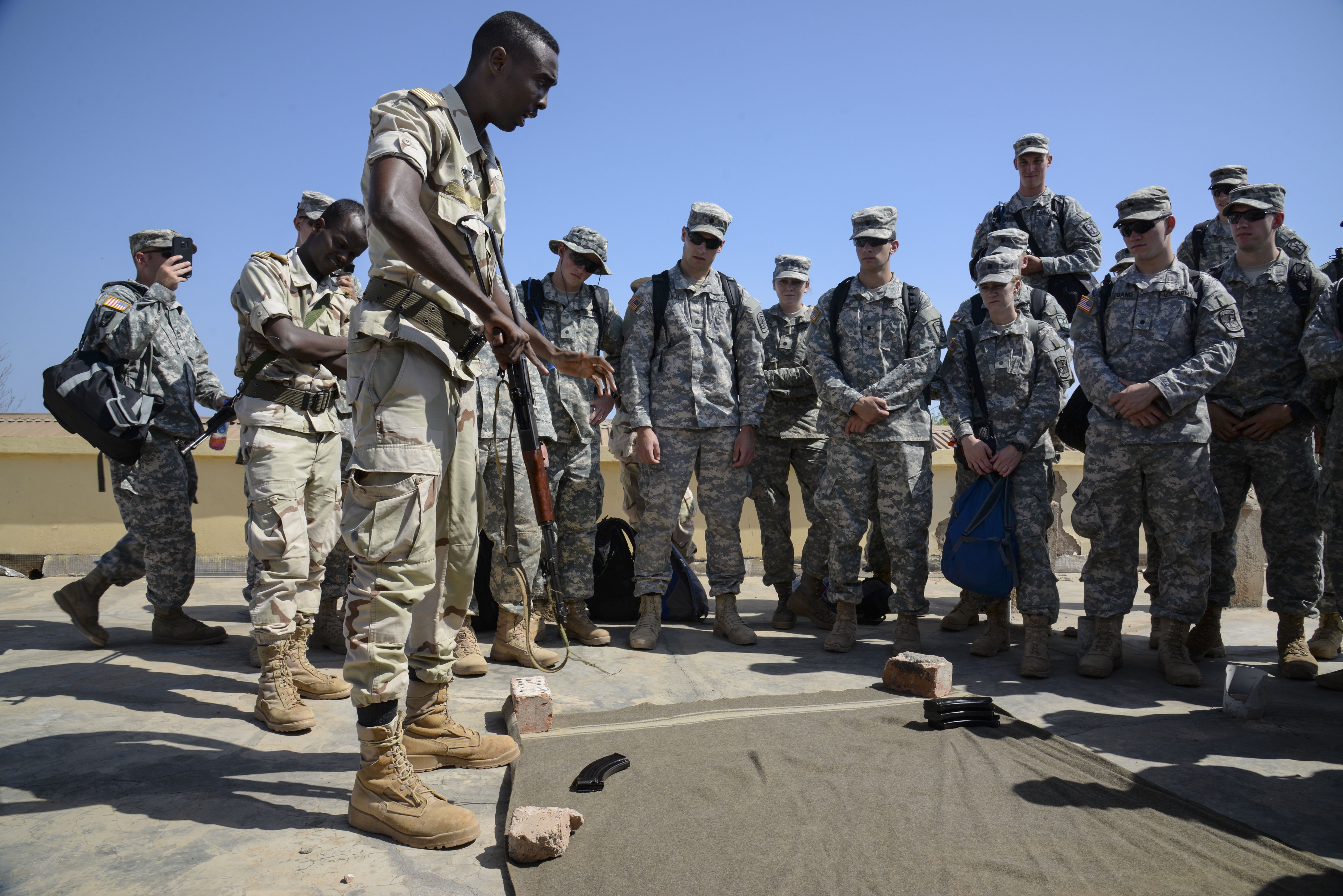 U.S. Army Reserve Officer Training Corps cadets watch as a Djiboutian Army weapons instructor teaches them how to safely field strip an AK-47 at the Djiboutian Army Academy in Arta, Djibouti, July 25, 2016. After the cadets learned the fundamentals, they competed with each other to see who could field strip the weapon quickest. (U.S. Air Force photo by Staff Sgt. Benjamin Raughton/Released)