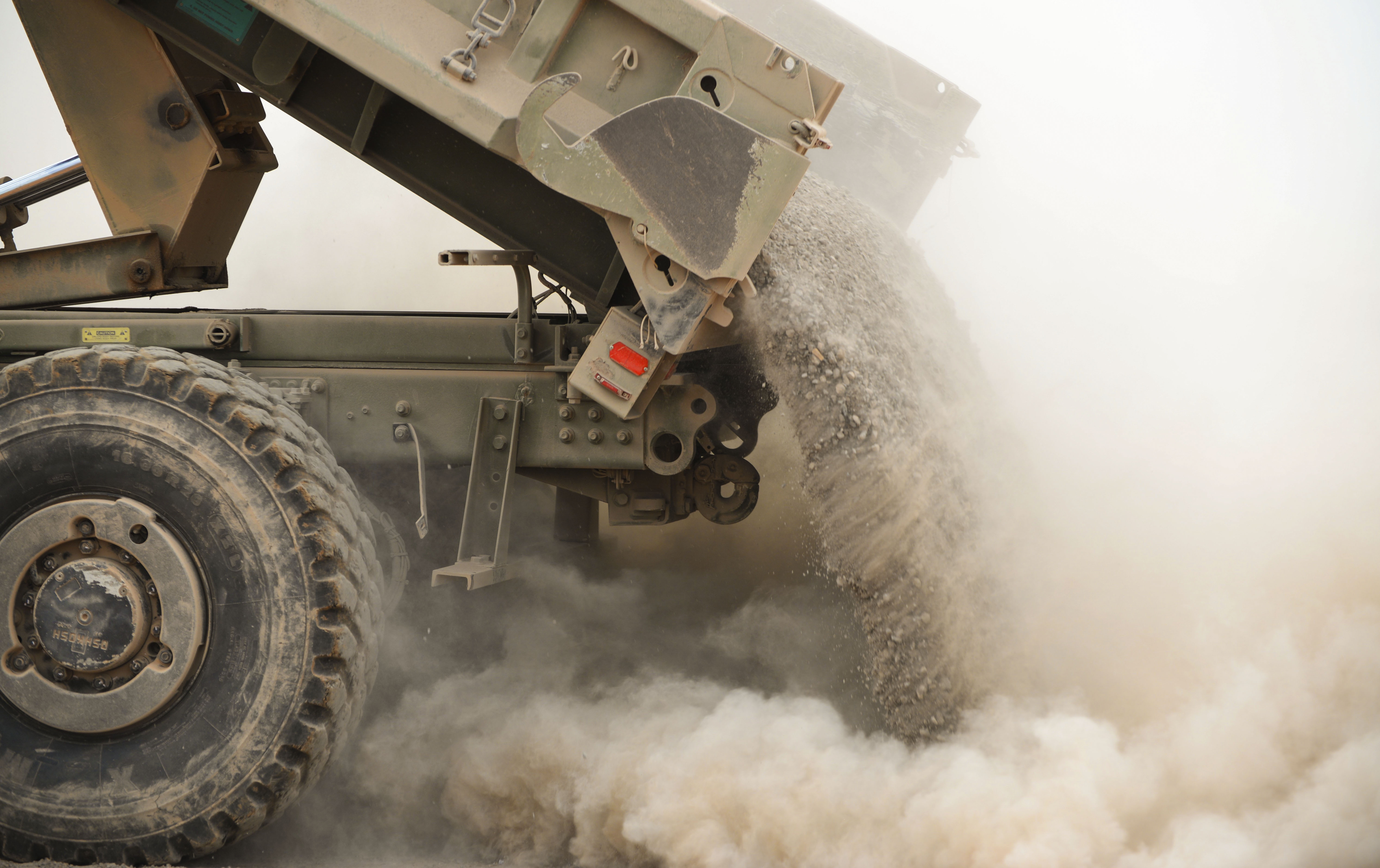 A dump truck releases gravel onto the ground to further construction of a parking pad at a Djibouti Airfield, July 28, 2016. Logistical delays, such as gravel delivery, occasionally delayed construction, but the Seabees completed the project ahead of schedule. (U.S. Air Force photo by Staff Sgt. Benjamin Raughton/Released)