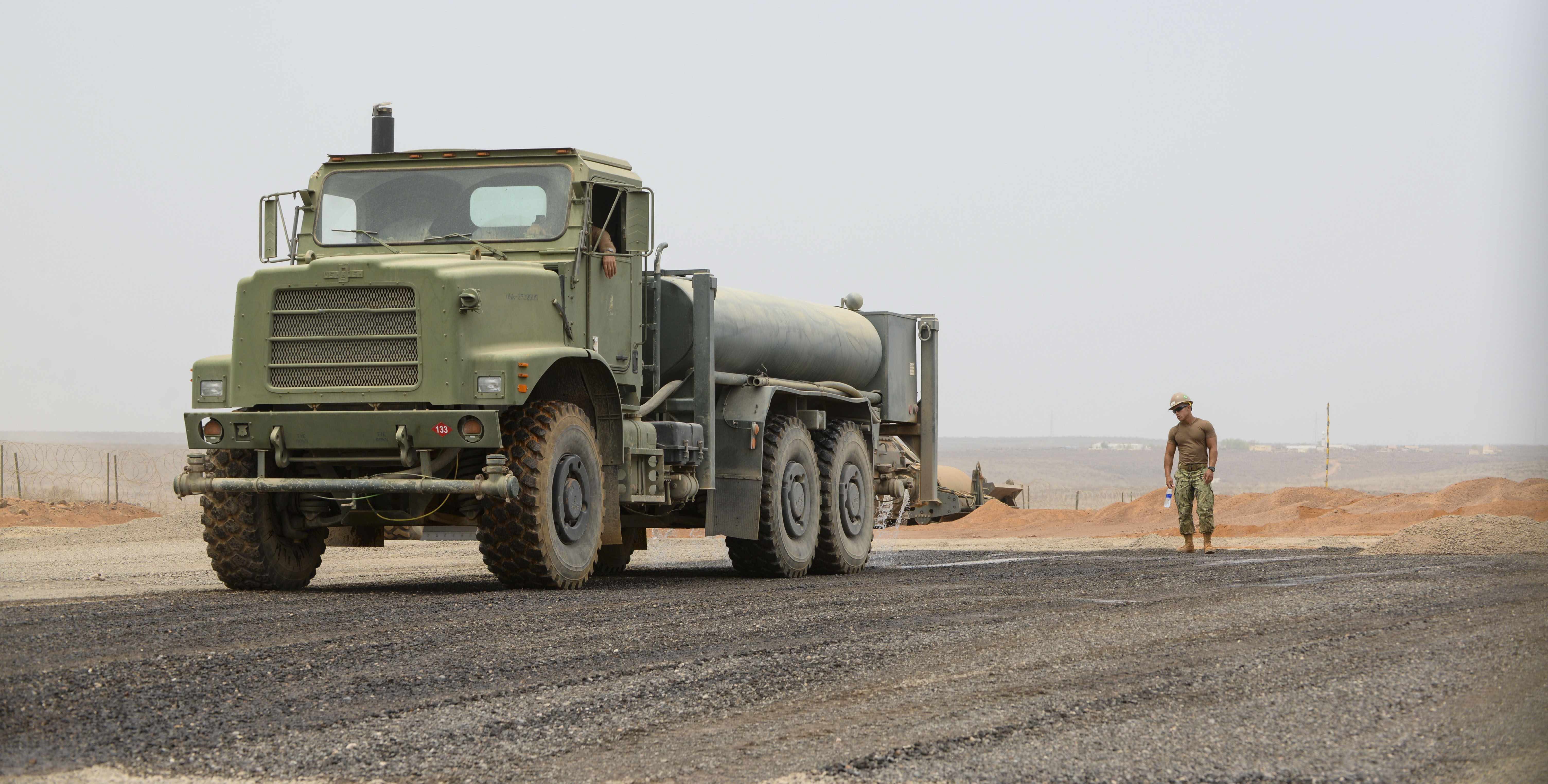 Petty Officer 2nd Class Tom Ross, Naval Mobile Construction Battalion 22 heavy equipment operator, drives a water truck over a gravel parking pad while Petty Officer 2nd Class Christian Rivera, NMCB 22 heavy equipment operator and team lead, watches his work at a Djibouti airfield, July 28, 2016. The water fell through the gravel, further compacting the surface and reducing dust. (U.S. Air Force photo by Staff Sgt. Benjamin Raughton/Released)